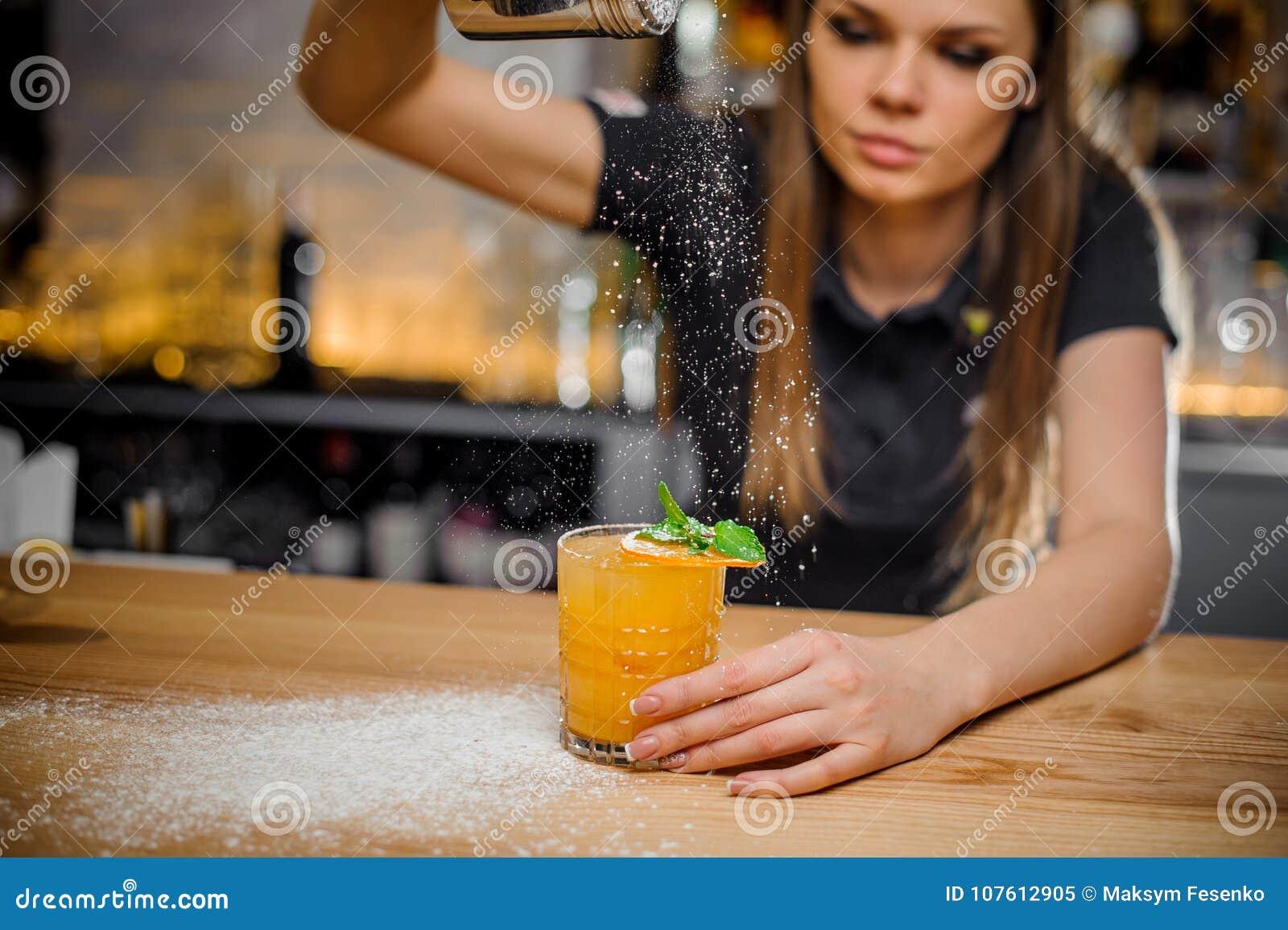 La barmaid finit la préparation du cocktail décorée de l orange en bon état et sèche
