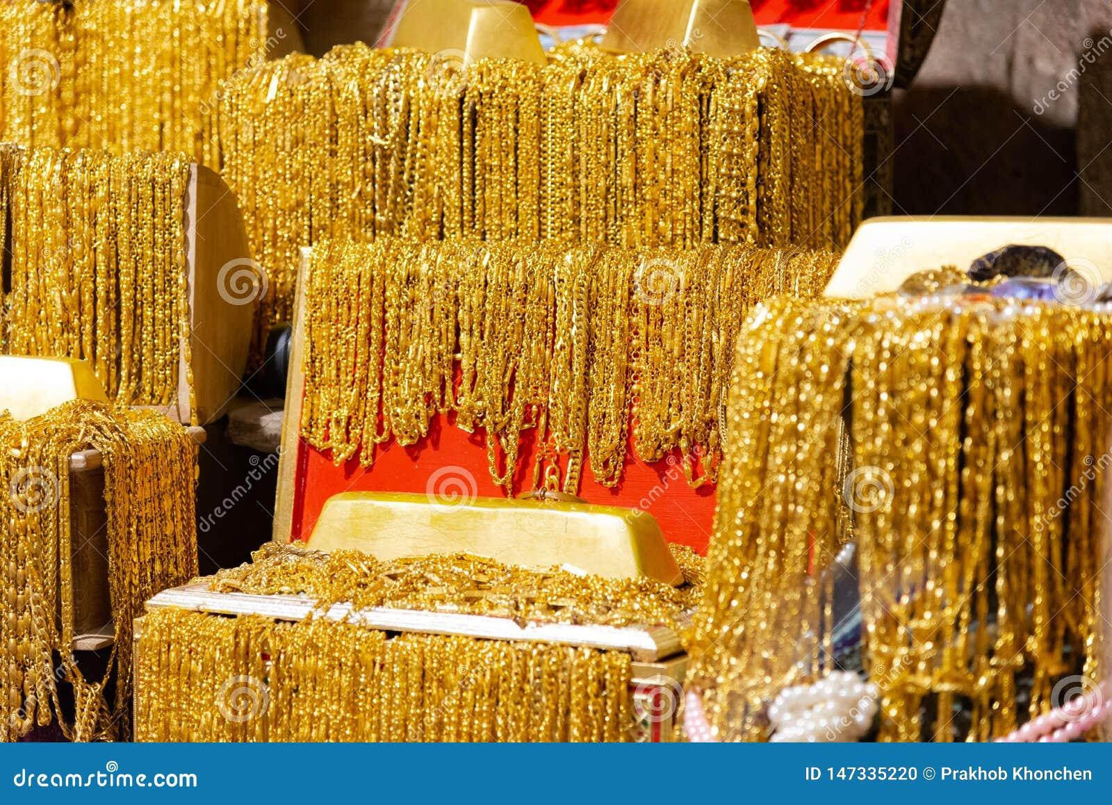 La barra di oro e la collana dell oro molti appendono sulla foto nera del fondo di struttura del vassoio del velluto