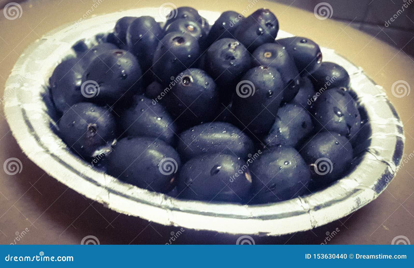 La baya comestible púrpura oscura llamada como Jamun sirvió en una placa de papel coloreada de plata