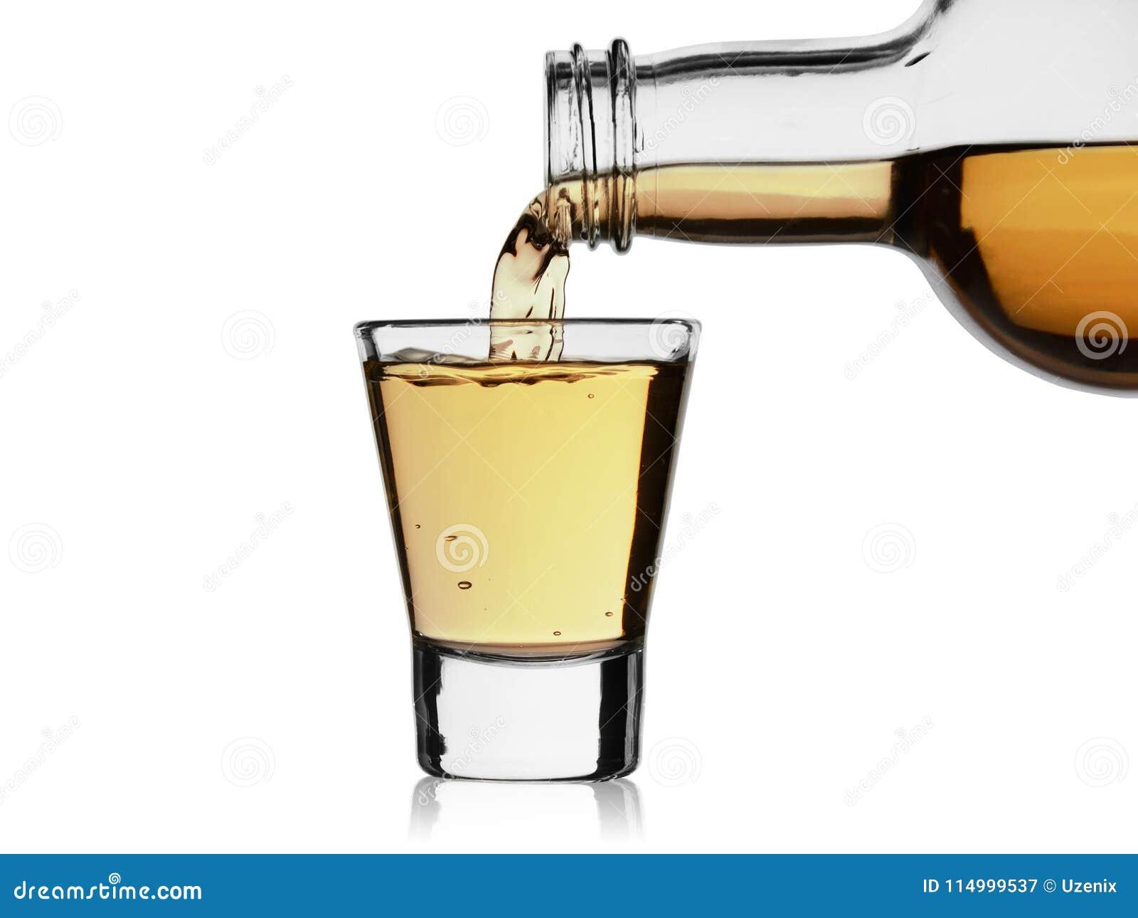 La bebida alcohólica vierte de una botella en un vidrio, aislado en un fondo blanco