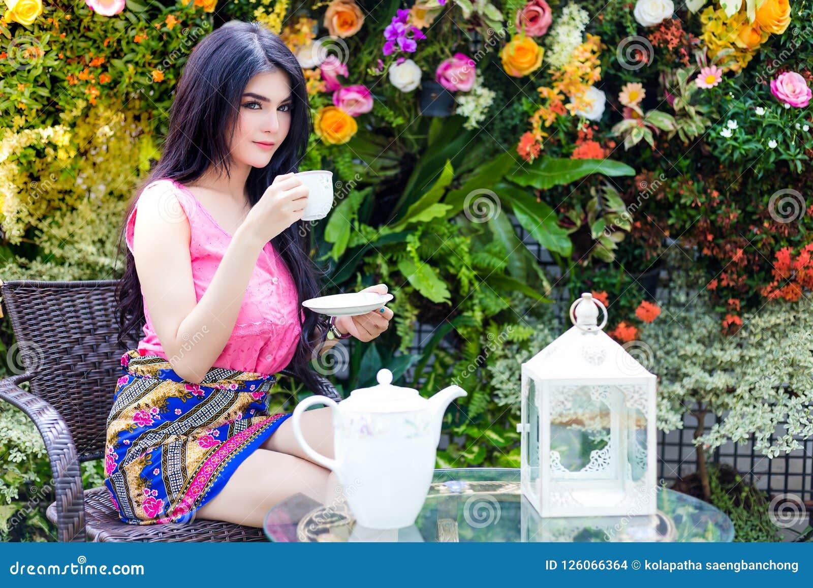 La bella donna affascinante sta bevendo il caffè o il tè nel pomeriggio