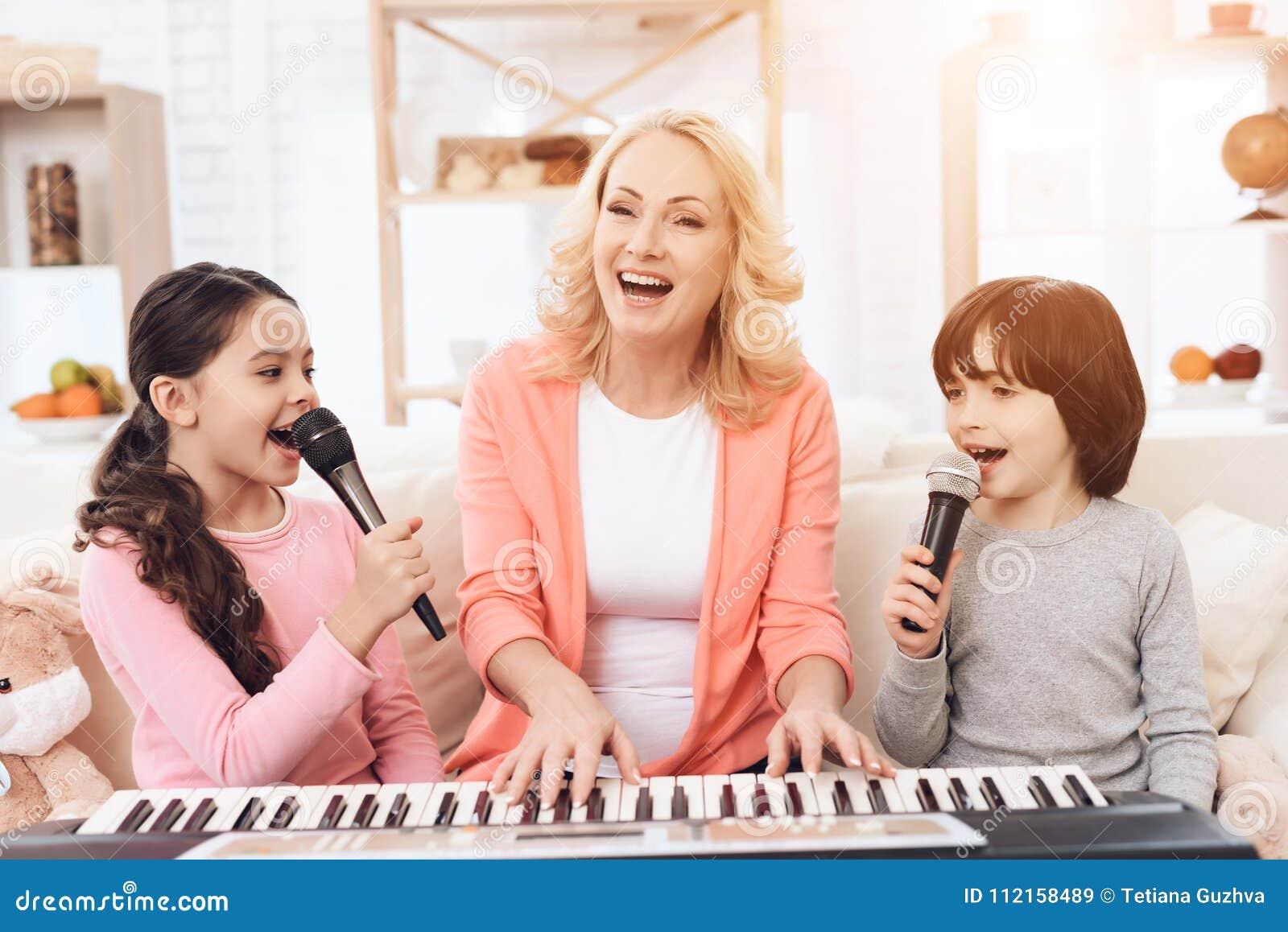 La bella donna anziana gioca sulla tastiera con i nipoti che cantano nel microfono