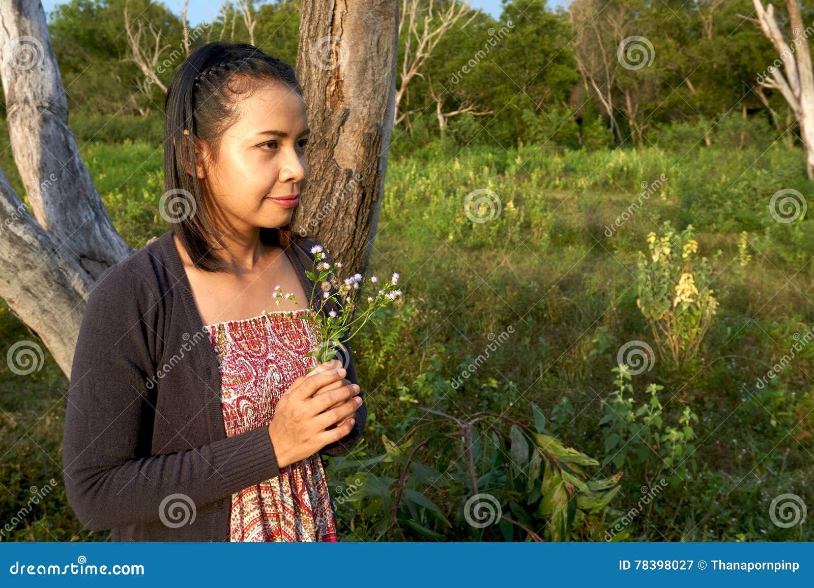 La bella donna asiatica è sorridente e tenente un gruppo di fiori selvaggi minuscoli in sua mano