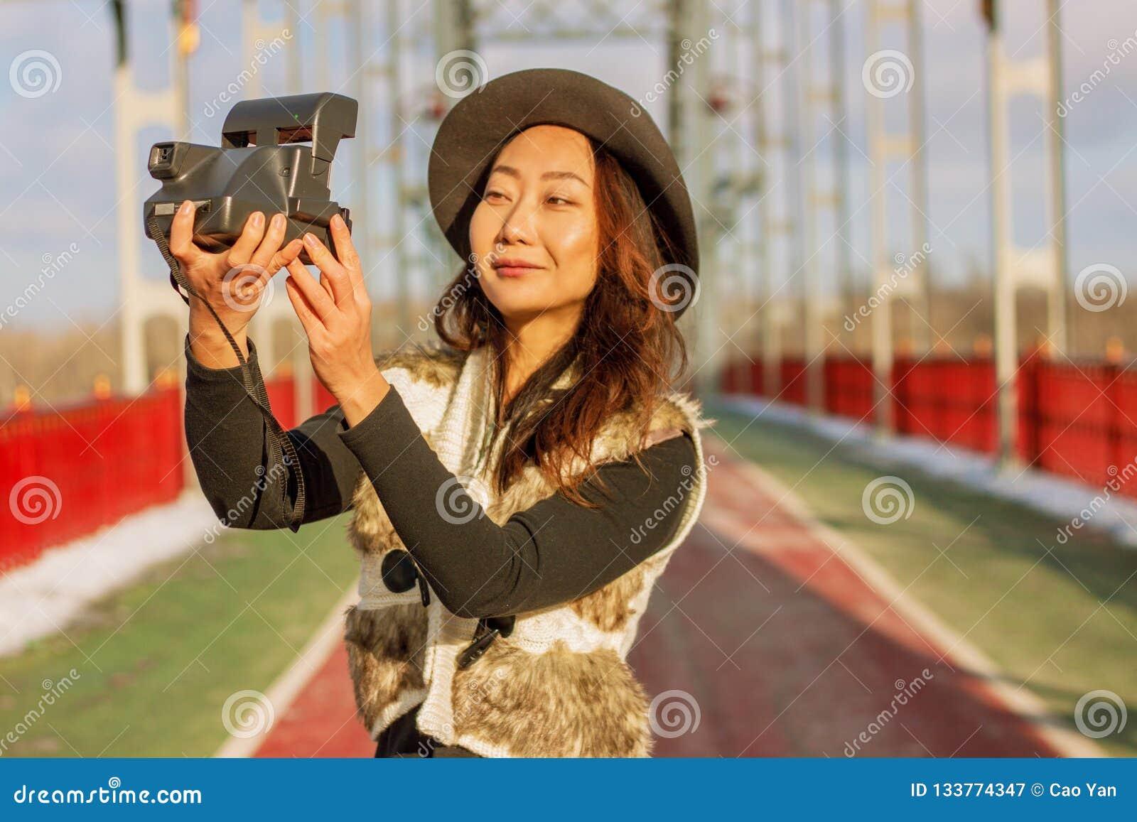 La bella donna in black hat fa un selfie della polaroid su un ponte nell inverno in Europa