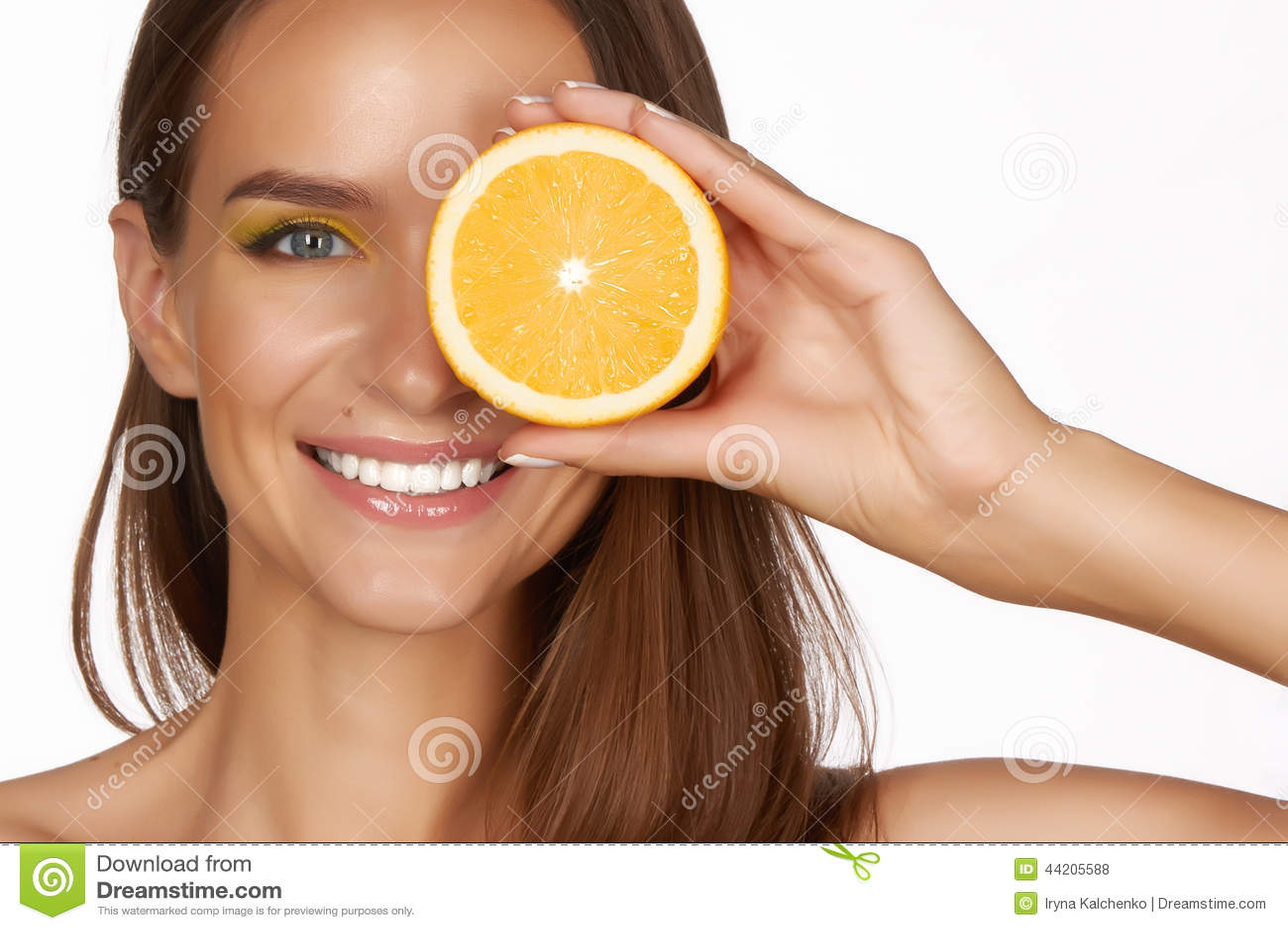 La bella donna castana sexy con l agrume su un fondo bianco, l alimento sano, l alimento saporito, dieta organica, sorride sano