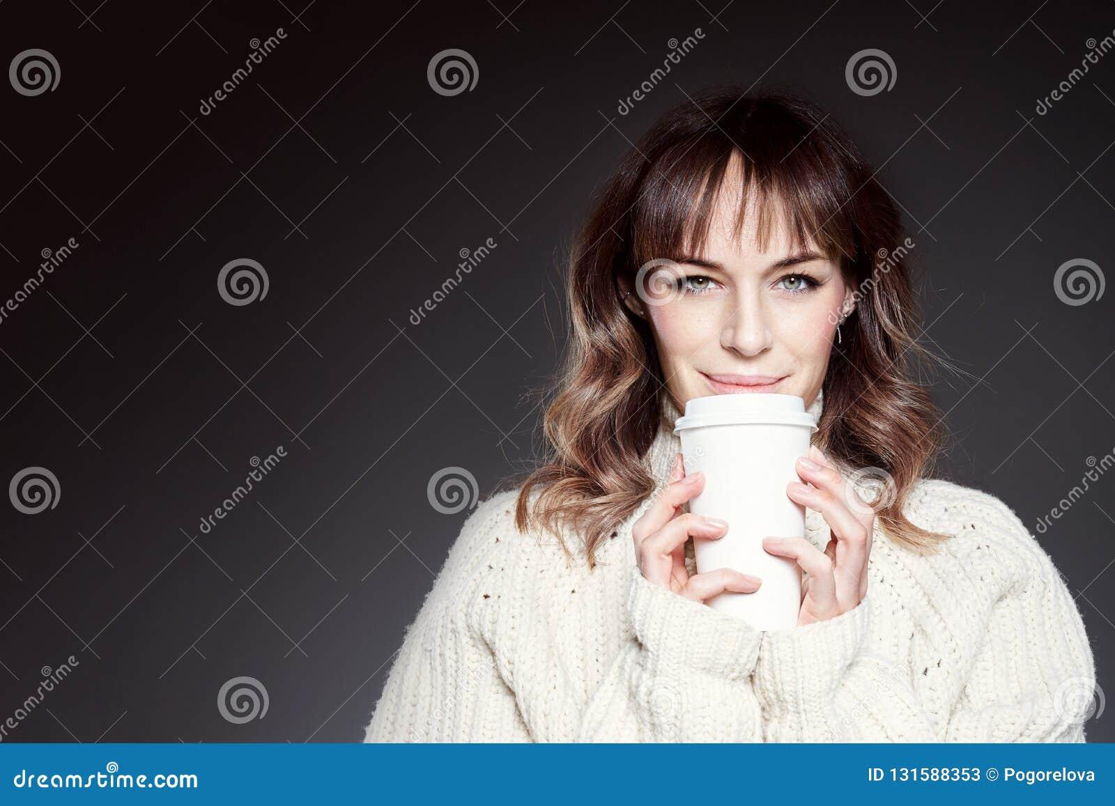 La bella donna con capelli lunghi che indossano le tenute rosse del maglione e del cappello mostra la tazza di caffè eliminabile