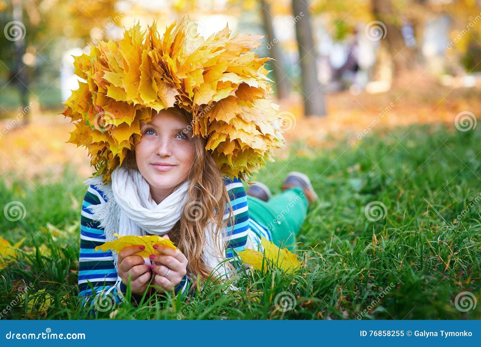 La bella donna con una corona di giallo lascia nel parco
