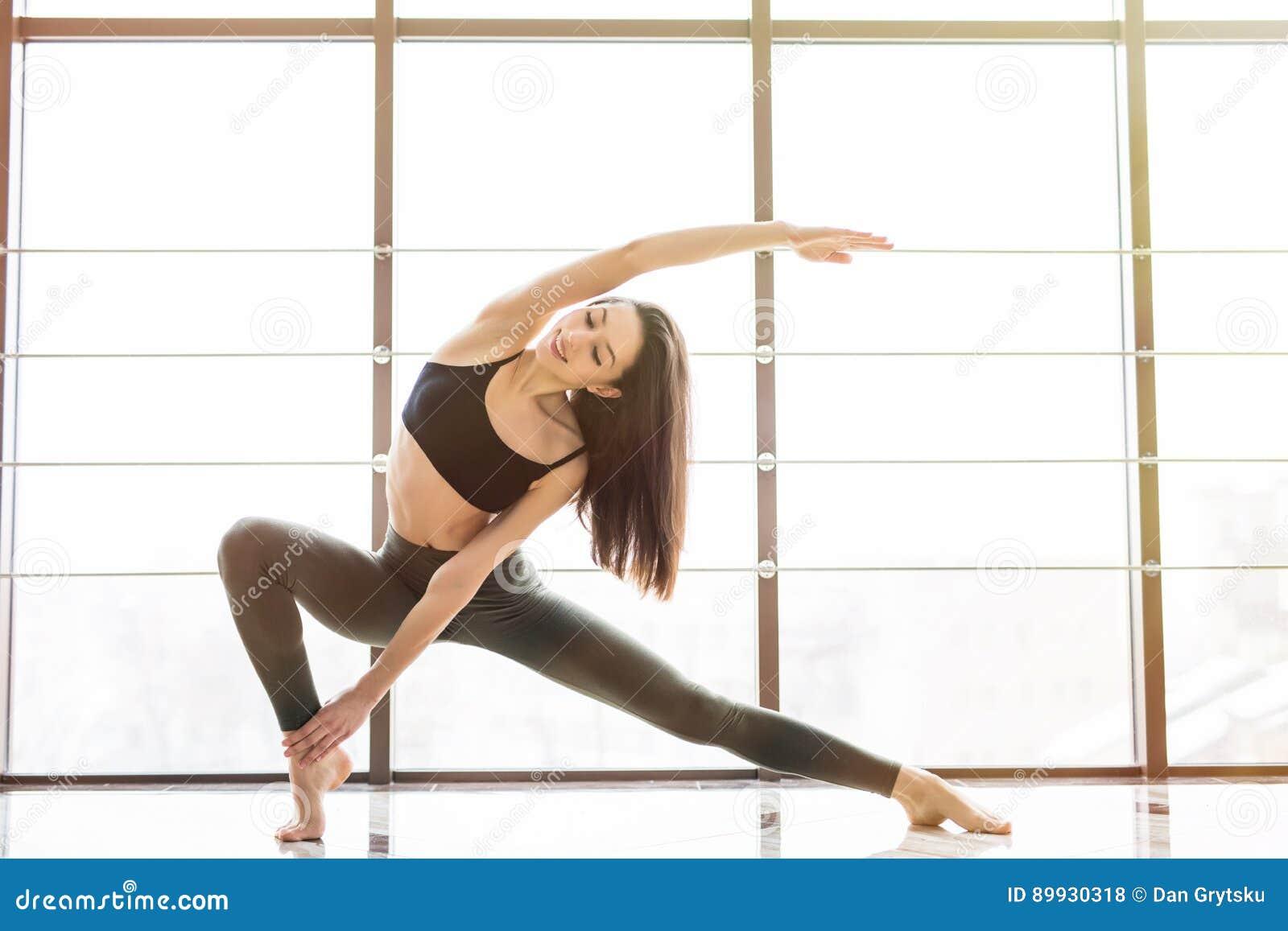 La bella donna pratica il asana Anjaneyasana di yoga in studio
