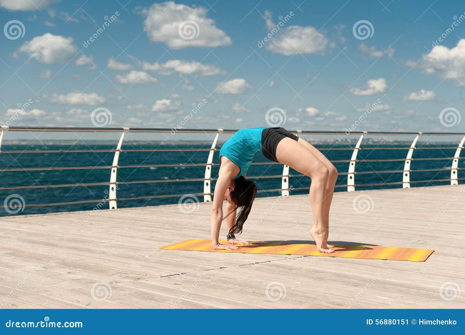 La bella donna pratica l yoga sul mare