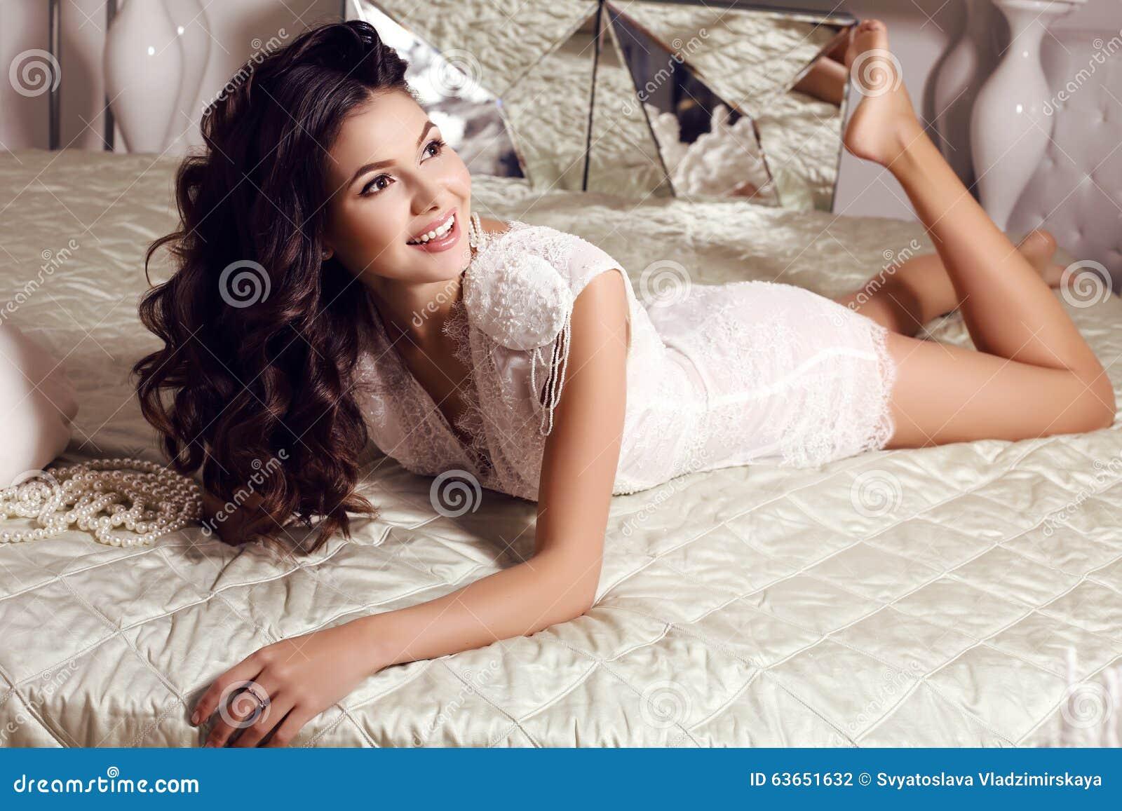La bella donna sensuale con capelli scuri lunghi indossa il vestito  elegante del pizzo b586ae0967d