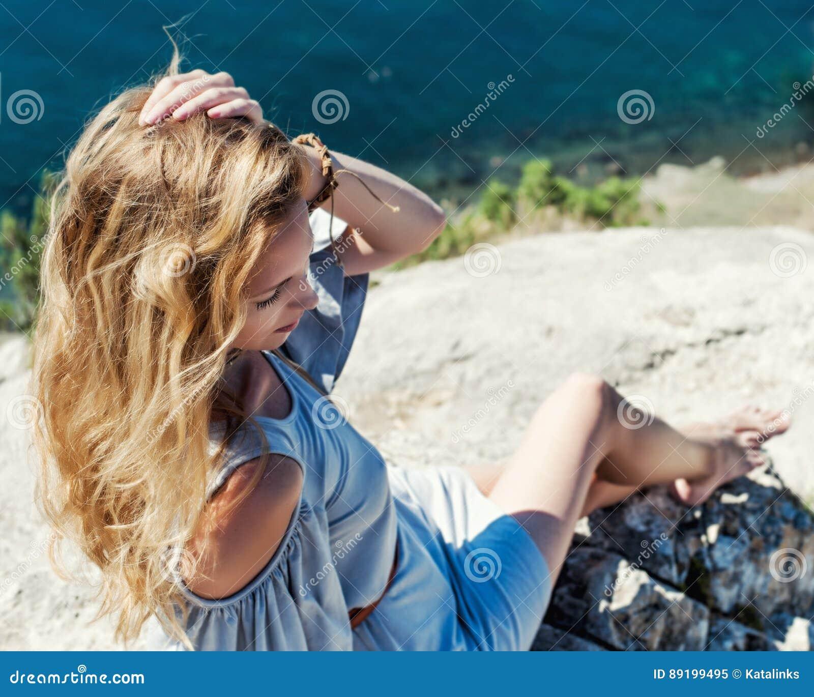 La bella donna si siede sull orlo della scogliera sopra i coas del mare