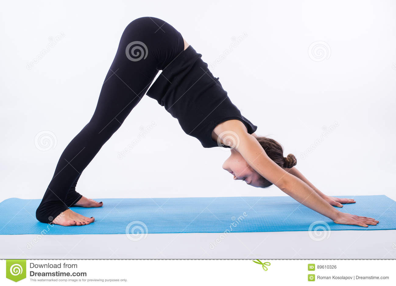 La bella donna sportiva di yogini di misura pratica lo svanasana di adhomukha di asana di yoga - posa orientata verso il basso de