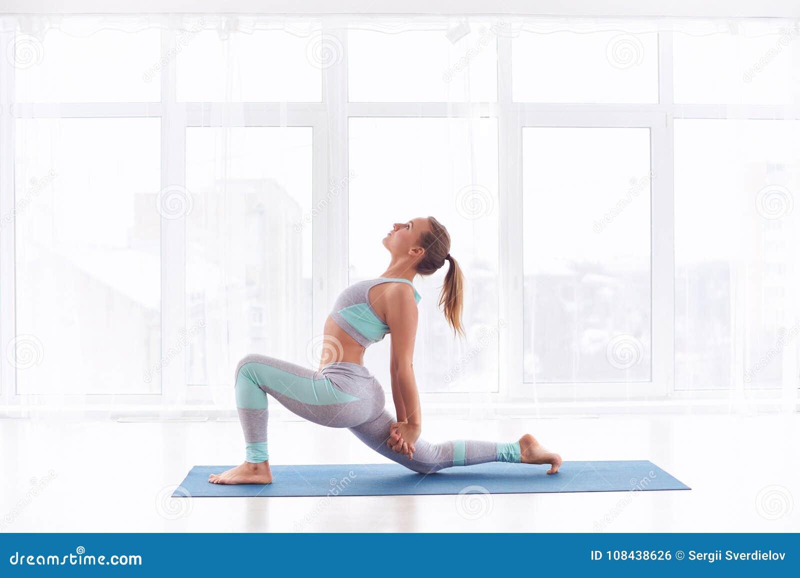 La bella donna sportiva di yogini di misura pratica il asana Ashva Sanchalasana - posa equestre di yoga allo studio di yoga