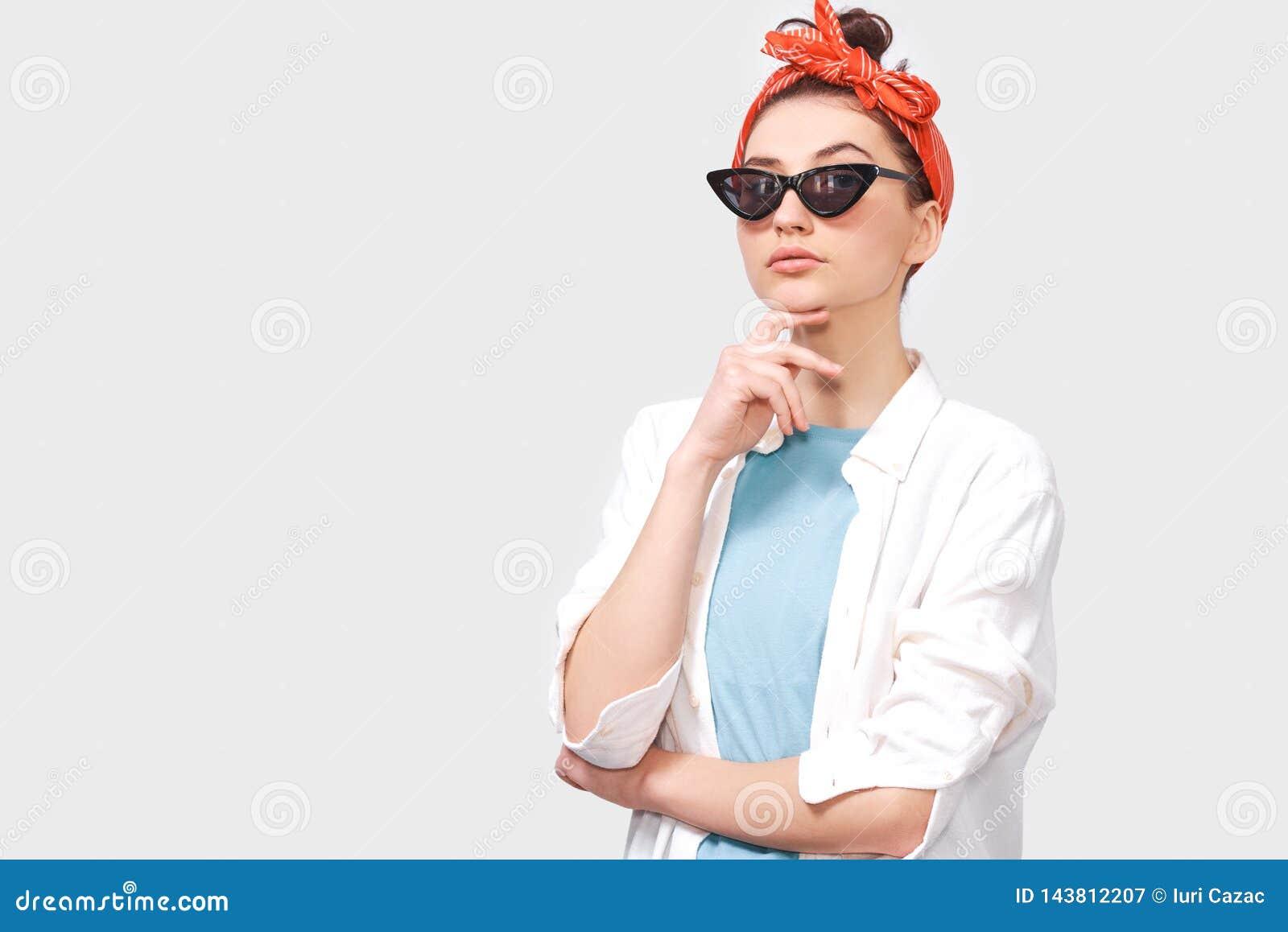 La bella giovane donna castana seria indossa gli occhiali da sole neri, la camicia bianca e la fascia rossa d avanguardia