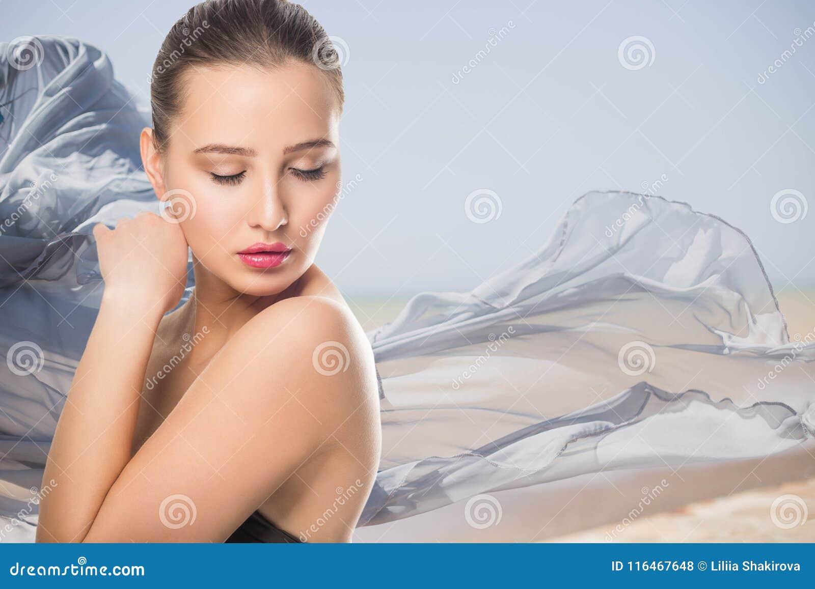 La bella giovane donna con il tocco fresco pulito della pelle possiede il fronte Trattamento facciale Cosmetologia, bellezza e st