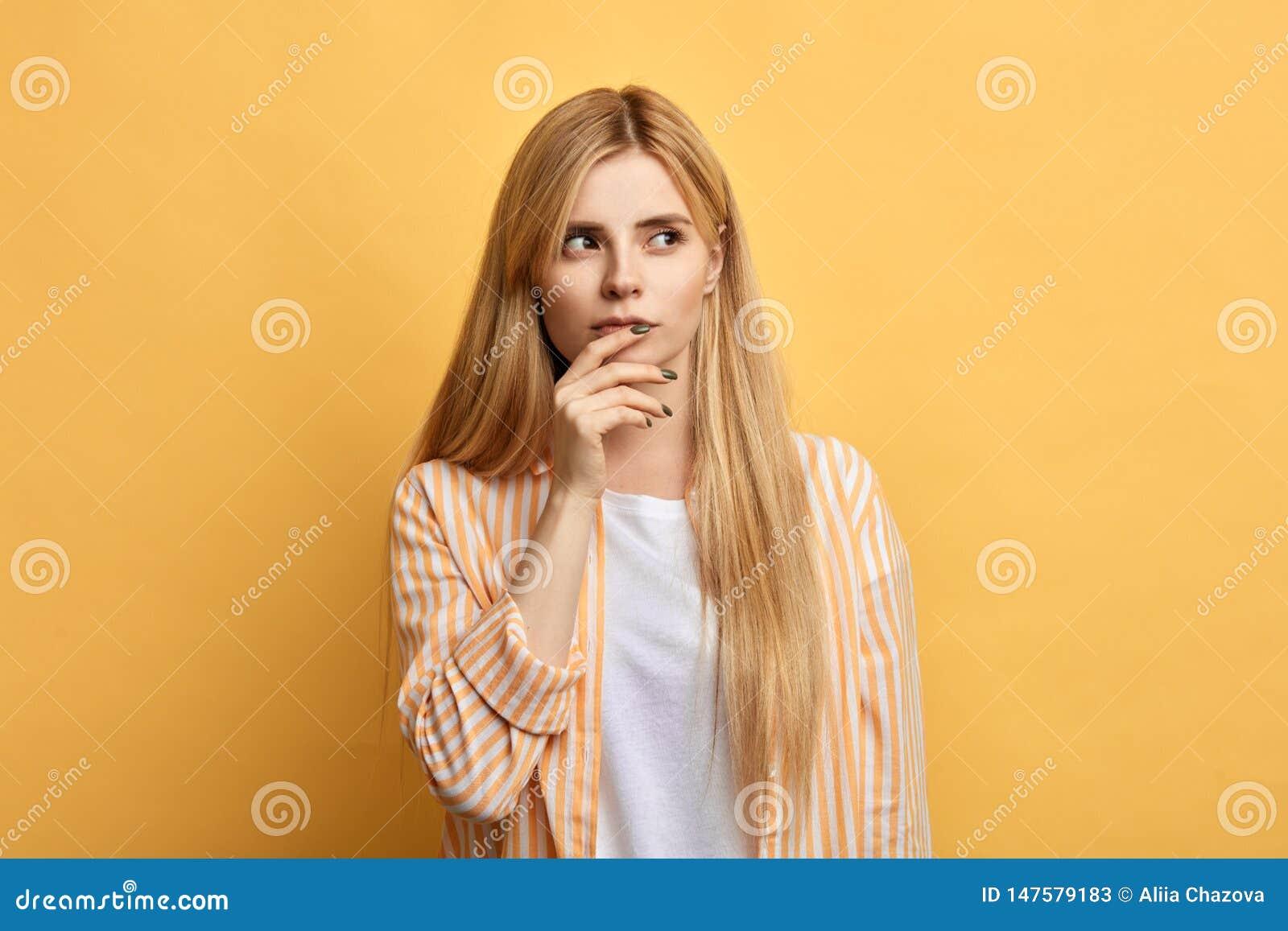 La bella giovane donna con le dita sulle sue labbra esprime l emozione confusa