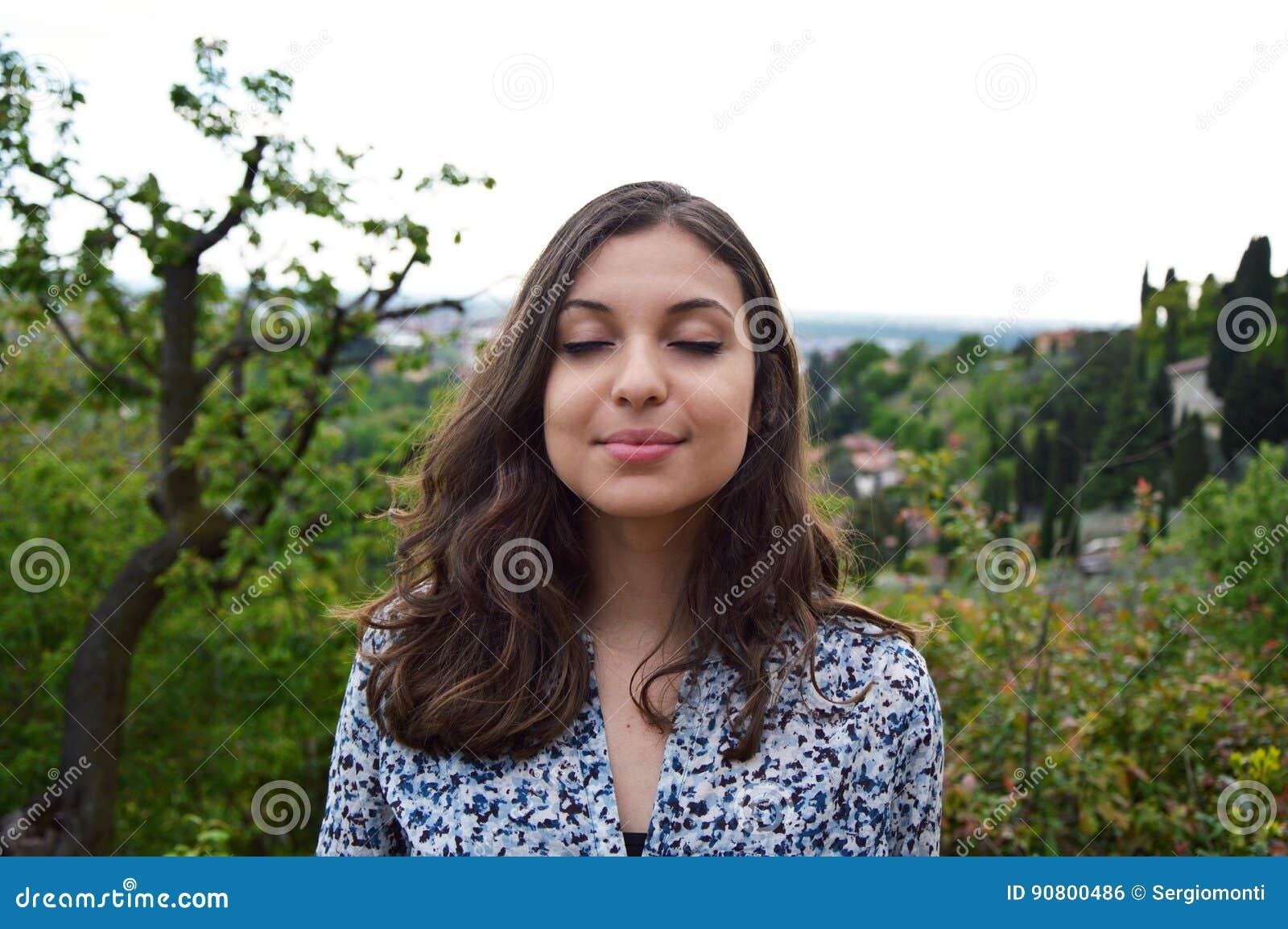 La bella giovane donna respira con gli occhi chiusi che gode della riflessione spirituale tranquilla di quiete di silenzio