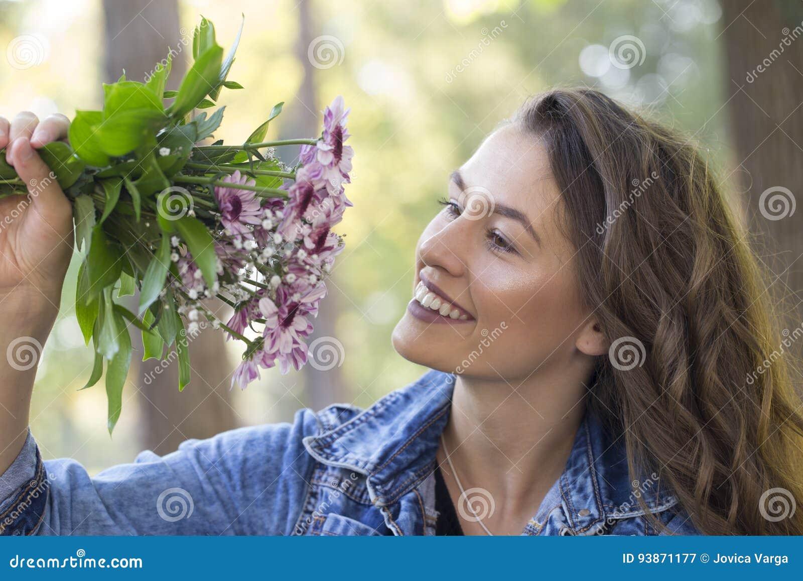 La bella giovane tenuta sorridente della donna fiorisce in sua mano