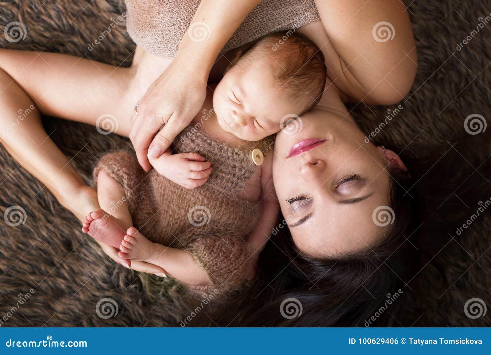 La bella madre che abbraccia con la tenerezza e se la preoccupa neonata