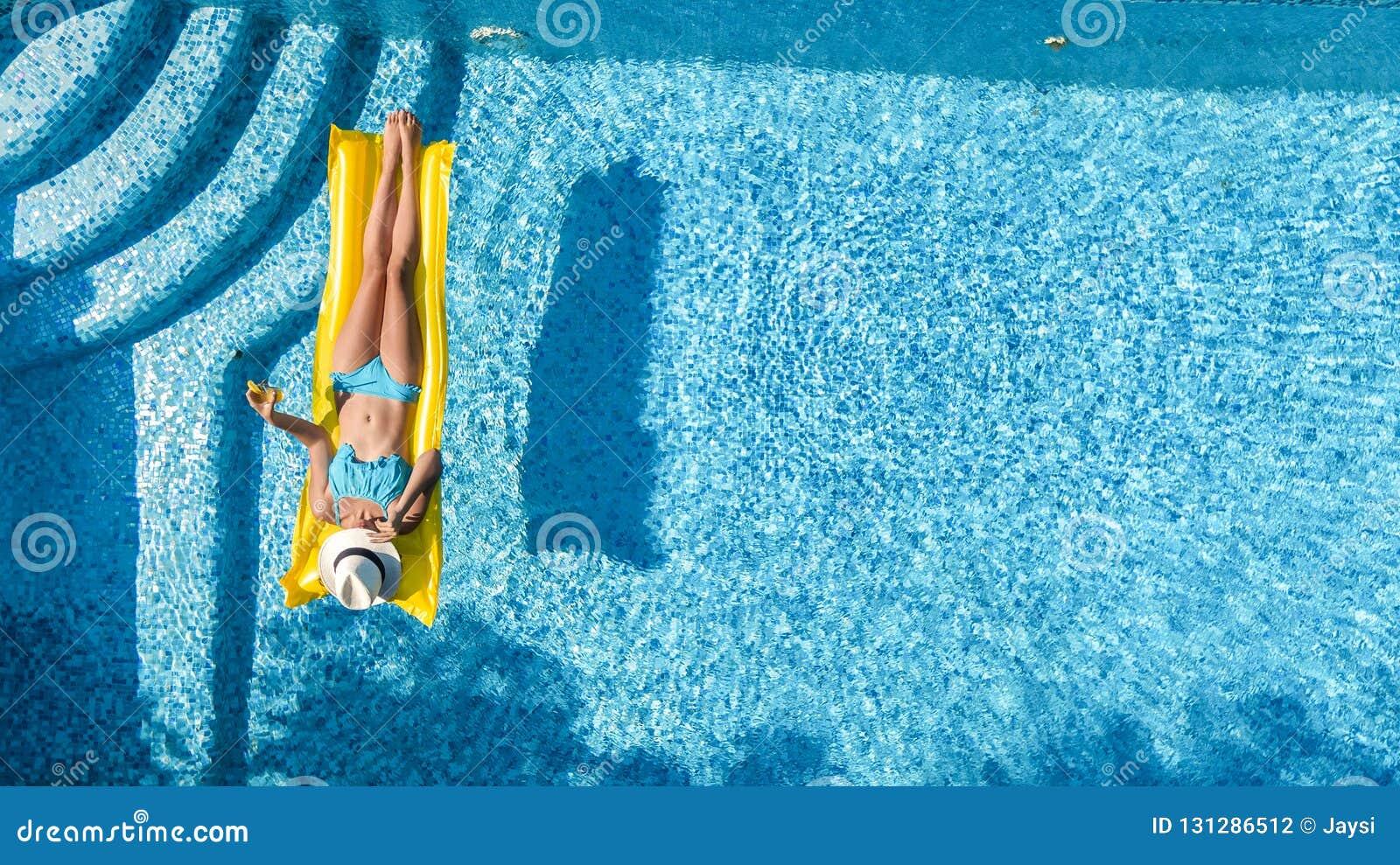 La bella ragazza che si rilassa nella piscina, nuotate sul materasso gonfiabile e si diverte in acqua sulla vacanza di famiglia
