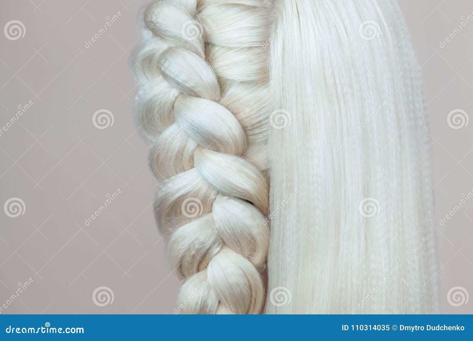 La bella ragazza con capelli biondi, parrucchiere tesse un primo piano della treccia, in un salone di bellezza