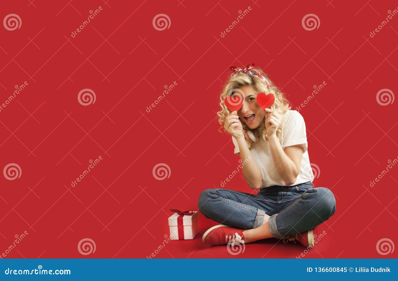 La bella ragazza con i cuori rossi e un regalo bianco con un arco si siede nella piena crescita un giorno dei backgroundValentine
