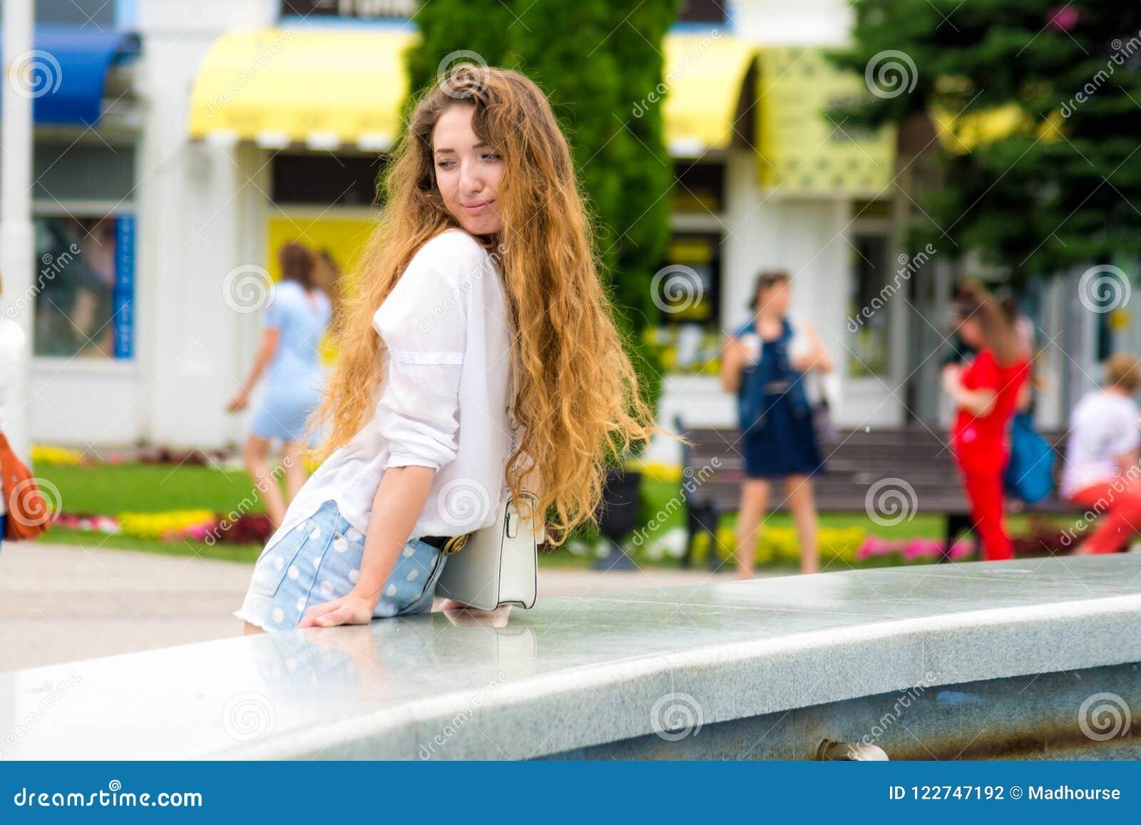 La bella ragazza esamina i passanti secondo la fontana nel parco