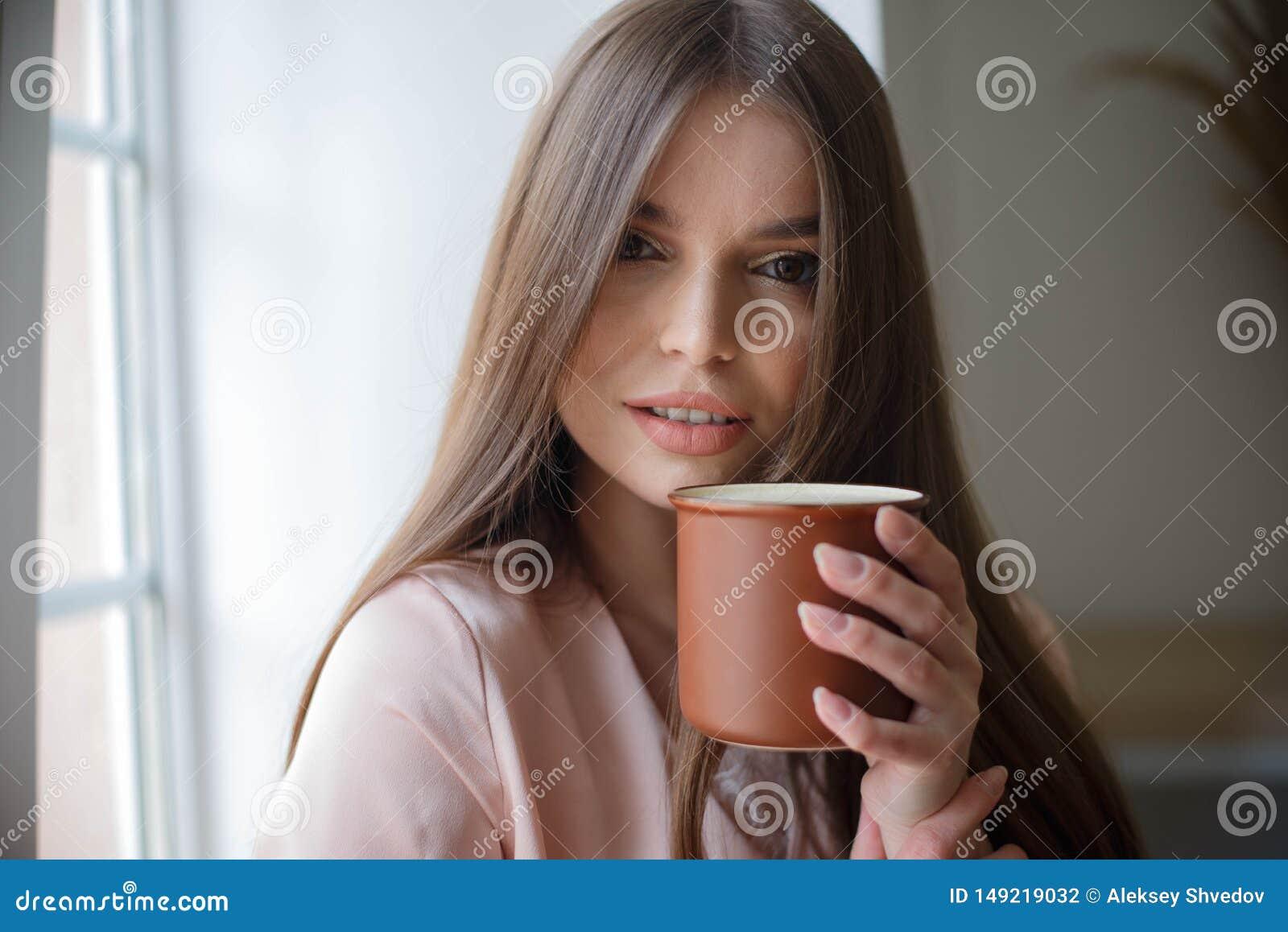 La bella ragazza sta bevendo il caff? e sta sorridendo mentre si sedeva al caff?
