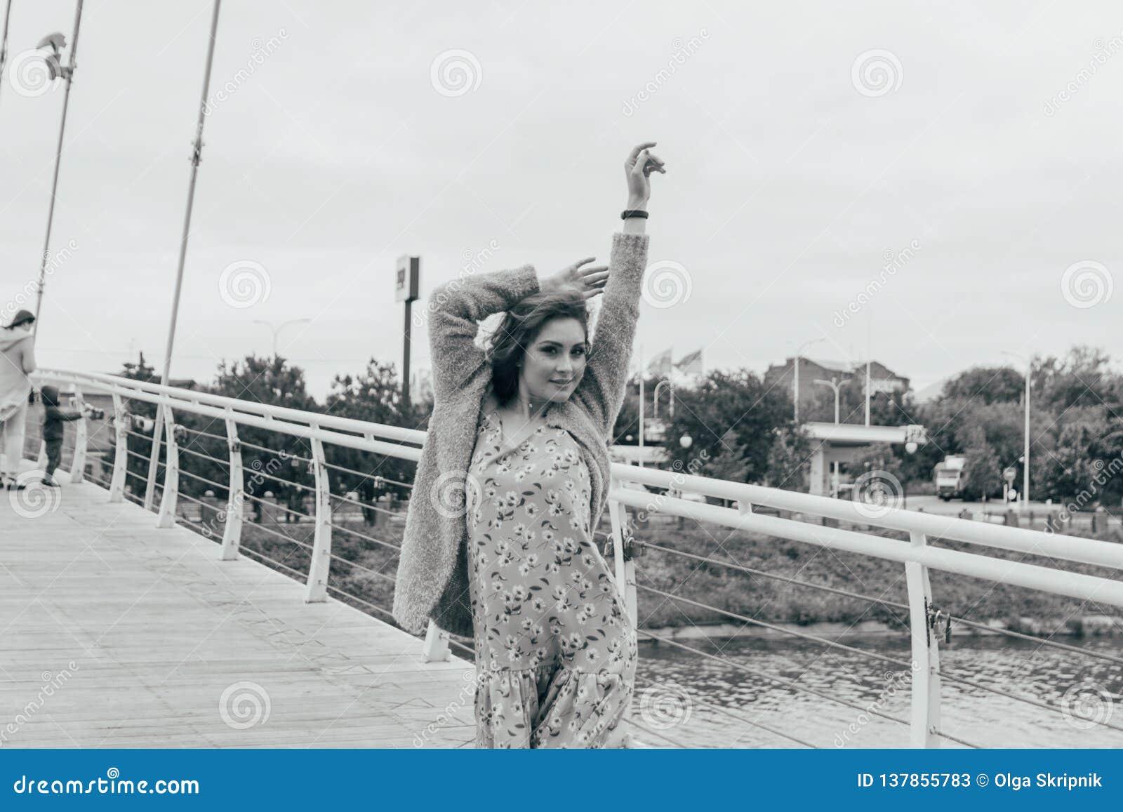 La bella ragazza sta sul ponte, il vento soffia nel suo fronte, sviluppante i suoi capelli Sorrisi della ragazza foto in bianco e
