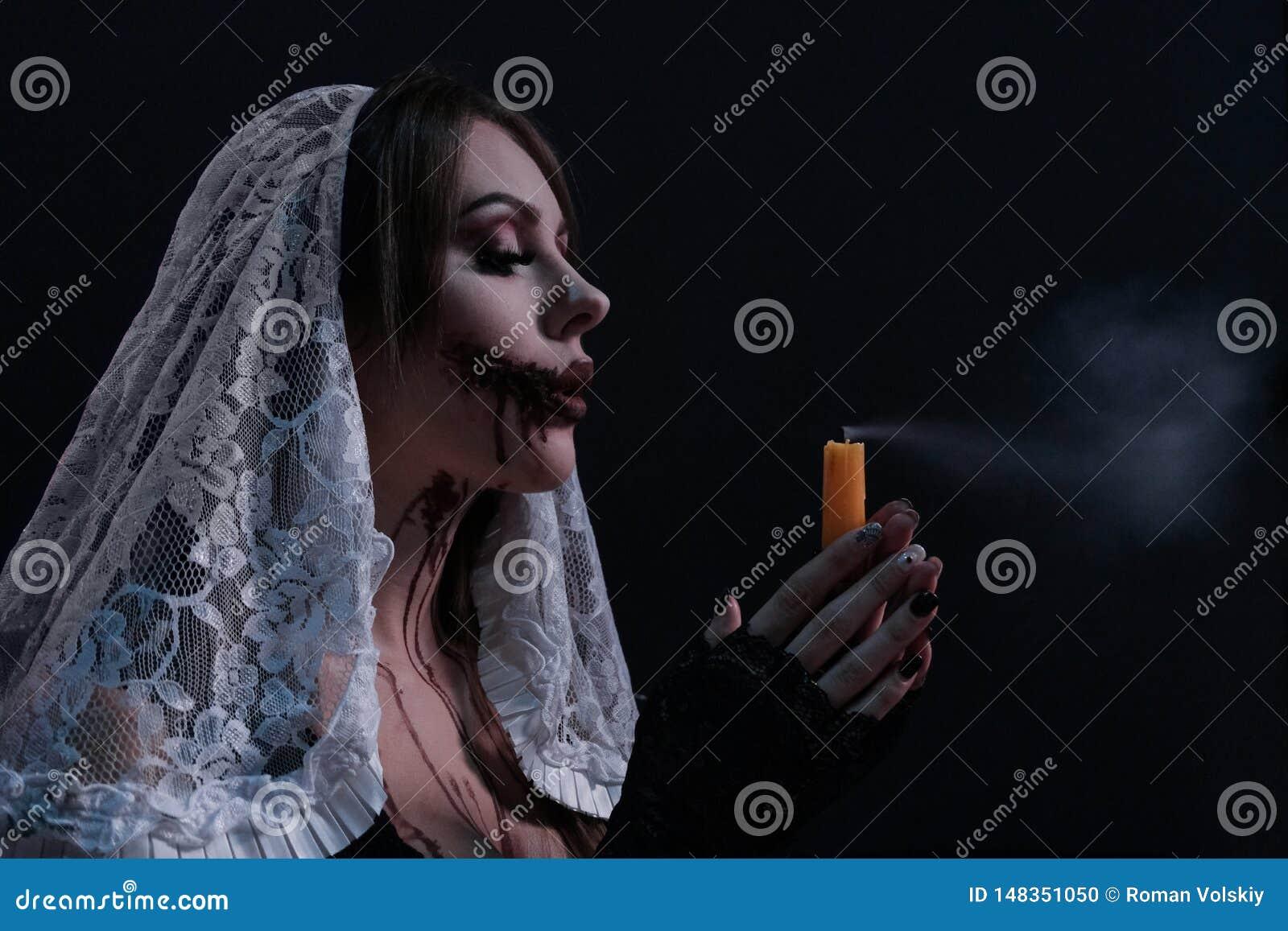 La bella ragazza in un costume terribile della suora spegne la candela Ritratto della donna con trucco di Halloween Concetto per