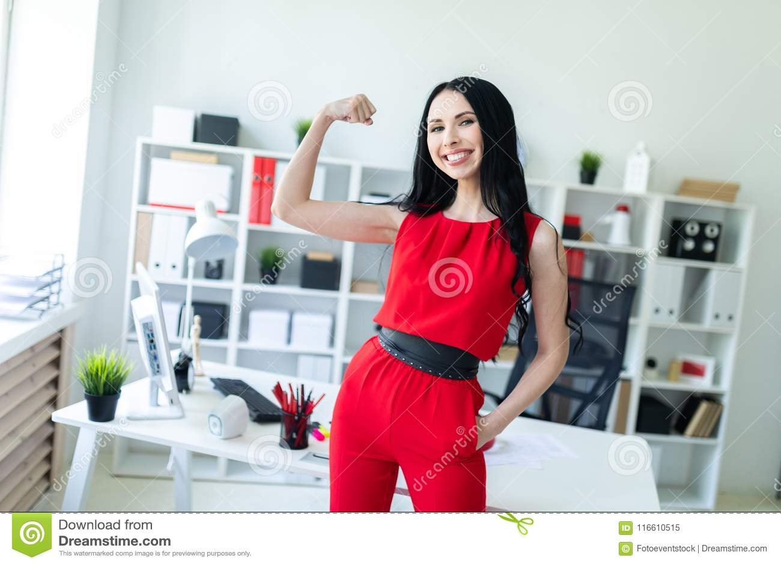 La bella ragazza in un vestito rosso sta nell ufficio e mostra un muscolo sul suo braccio