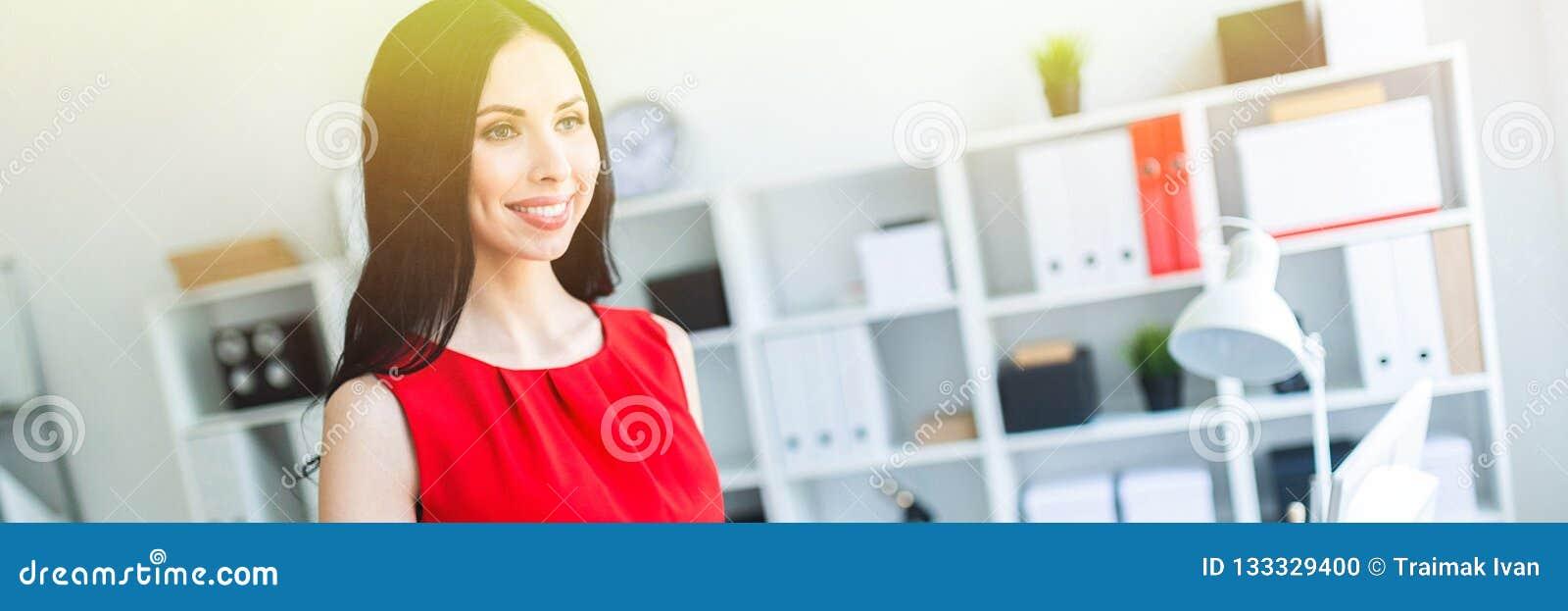 La bella ragazza in un vestito rosso sta stando nell ufficio e sta tenendo un taccuino e un vetro di caffè