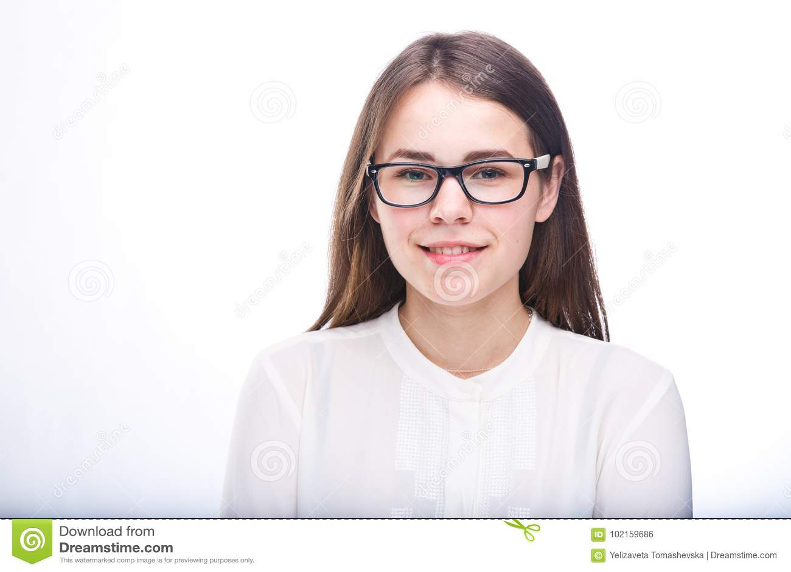 La bella ragazza in vetri con la struttura nera, con capelli marroni sopra le spalle e la camicia bianca su bianco ha isolato il