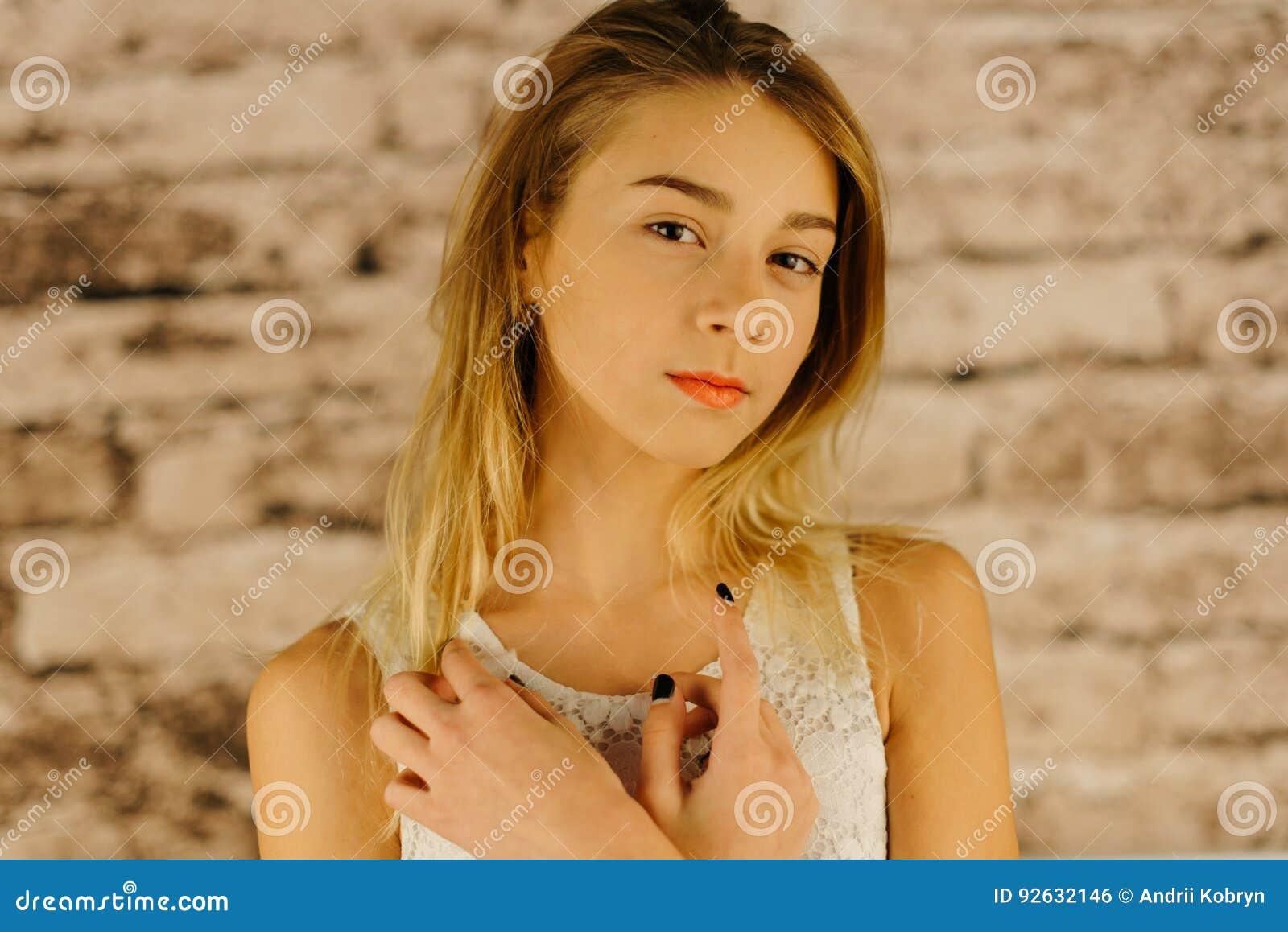 La belle adolescente sérieuse avec les cheveux blonds La verticale de plan rapproché