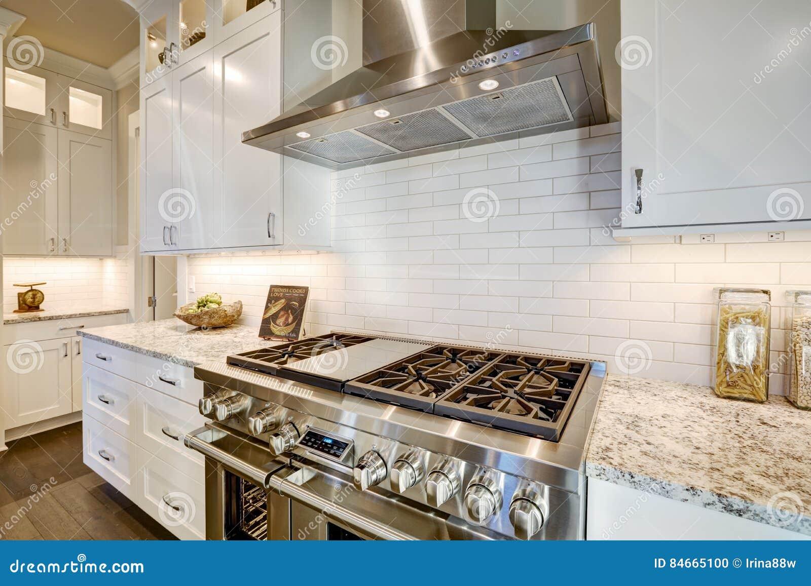 La belle cuisine comporte un recoin rempli de fourneau en acier