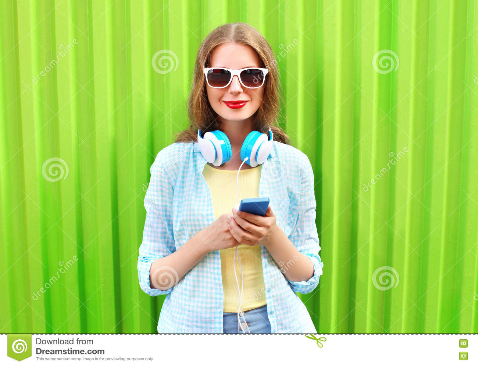 La belle femme écoute la musique dans des écouteurs utilisant le smartphone au-dessus du vert