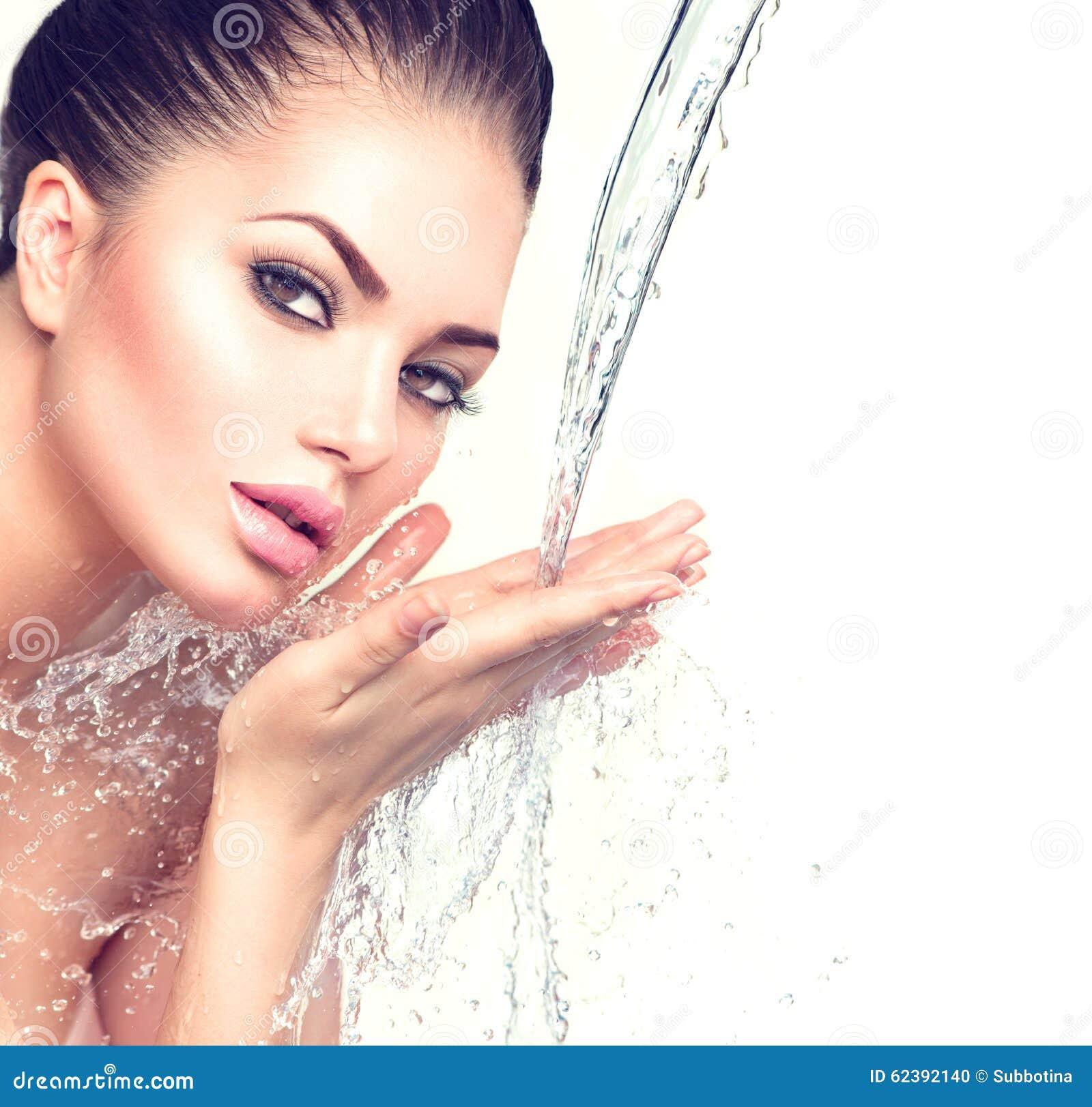 La belle femme avec éclabousse de l eau dans des ses mains