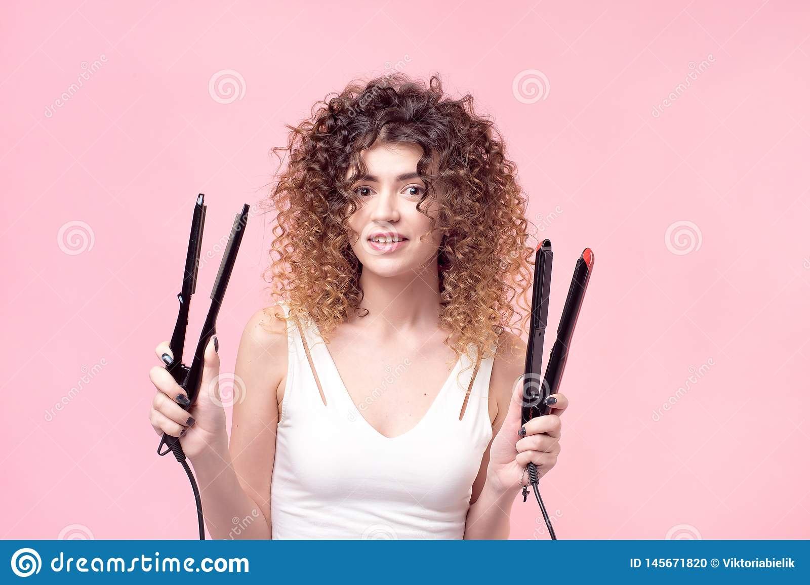 La belle femme avec les boucles stup?fiantes dans la chemise blanche tient d?nommer des accessoires ? disposition Cheveux dénomma