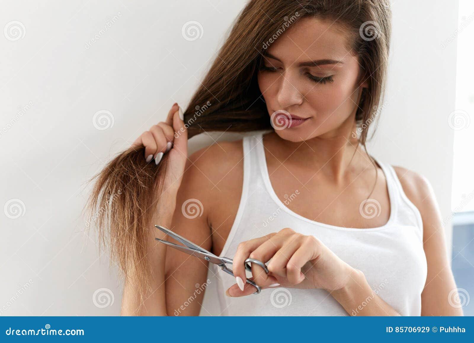 La belle femme coupe les pointes fourchues de longs cheveux avec des ciseaux