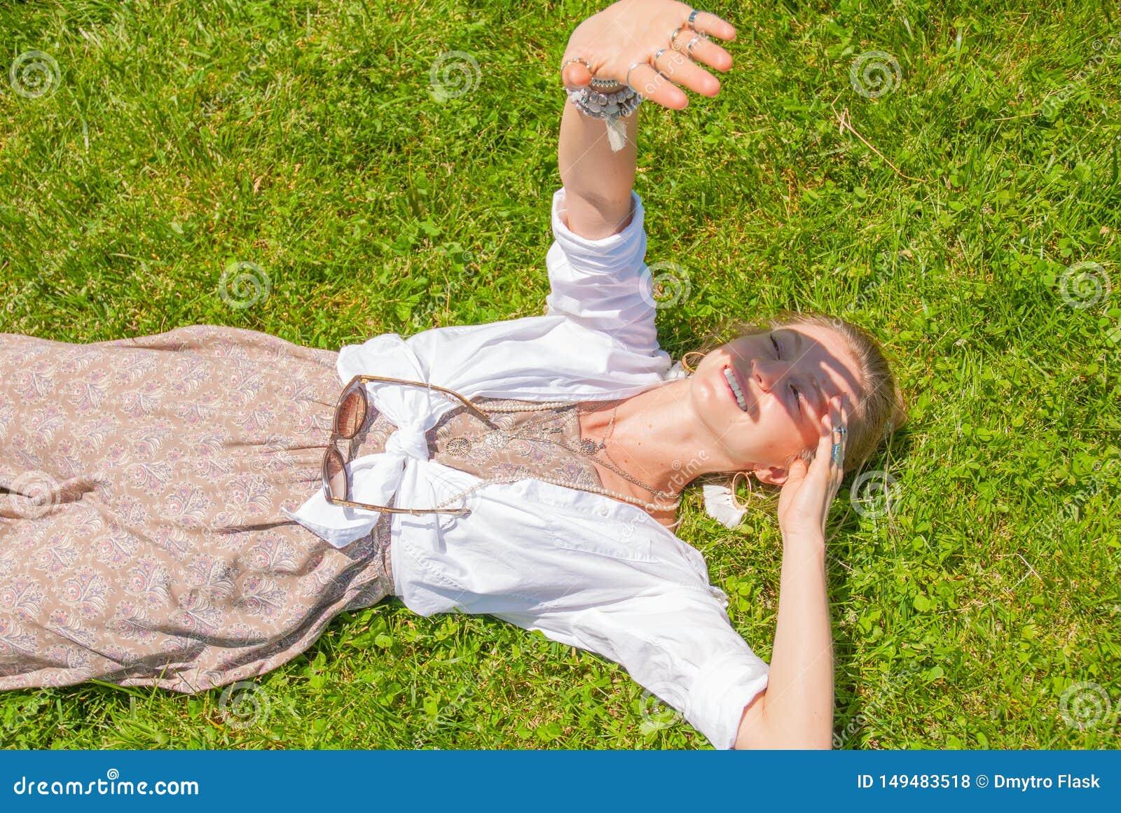 La belle femme de style de boho avec beaucoup d accessoires se trouve sur l herbe verte Mometn heureux
