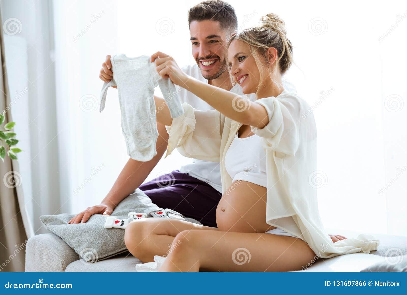 La belle femme enceinte et son mari regardent des vêtements de bébé sur le sofa à la maison
