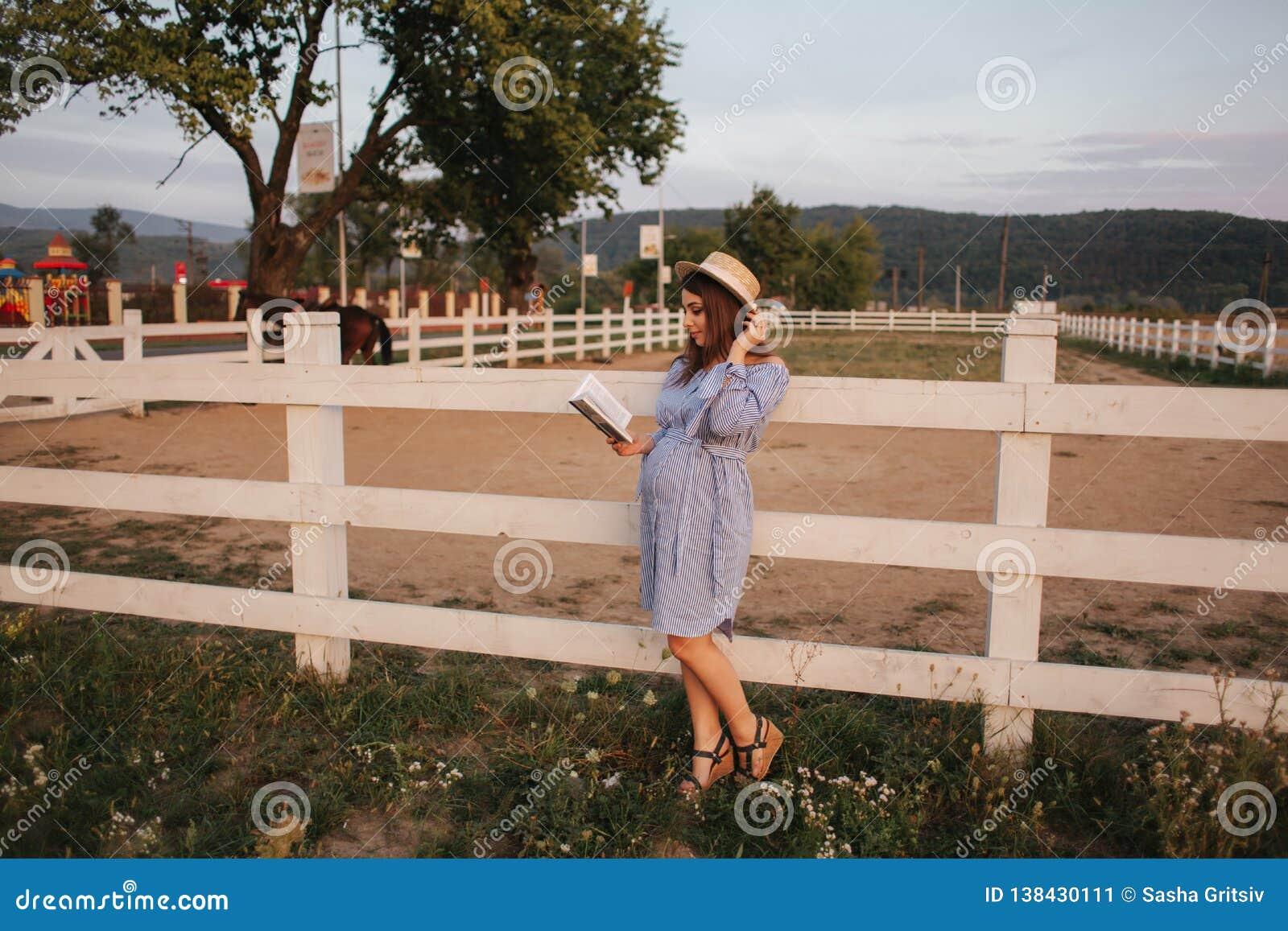 La belle femme enceinte a lu le livre sur la ferme Elle se tiennent prêt le fance et examinent le livre détendez