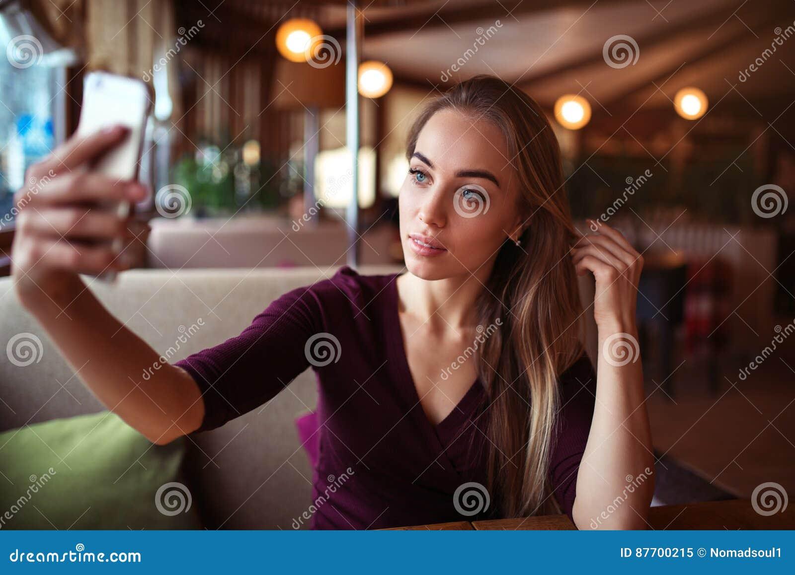 La belle femme font le selfie dans le restaurant