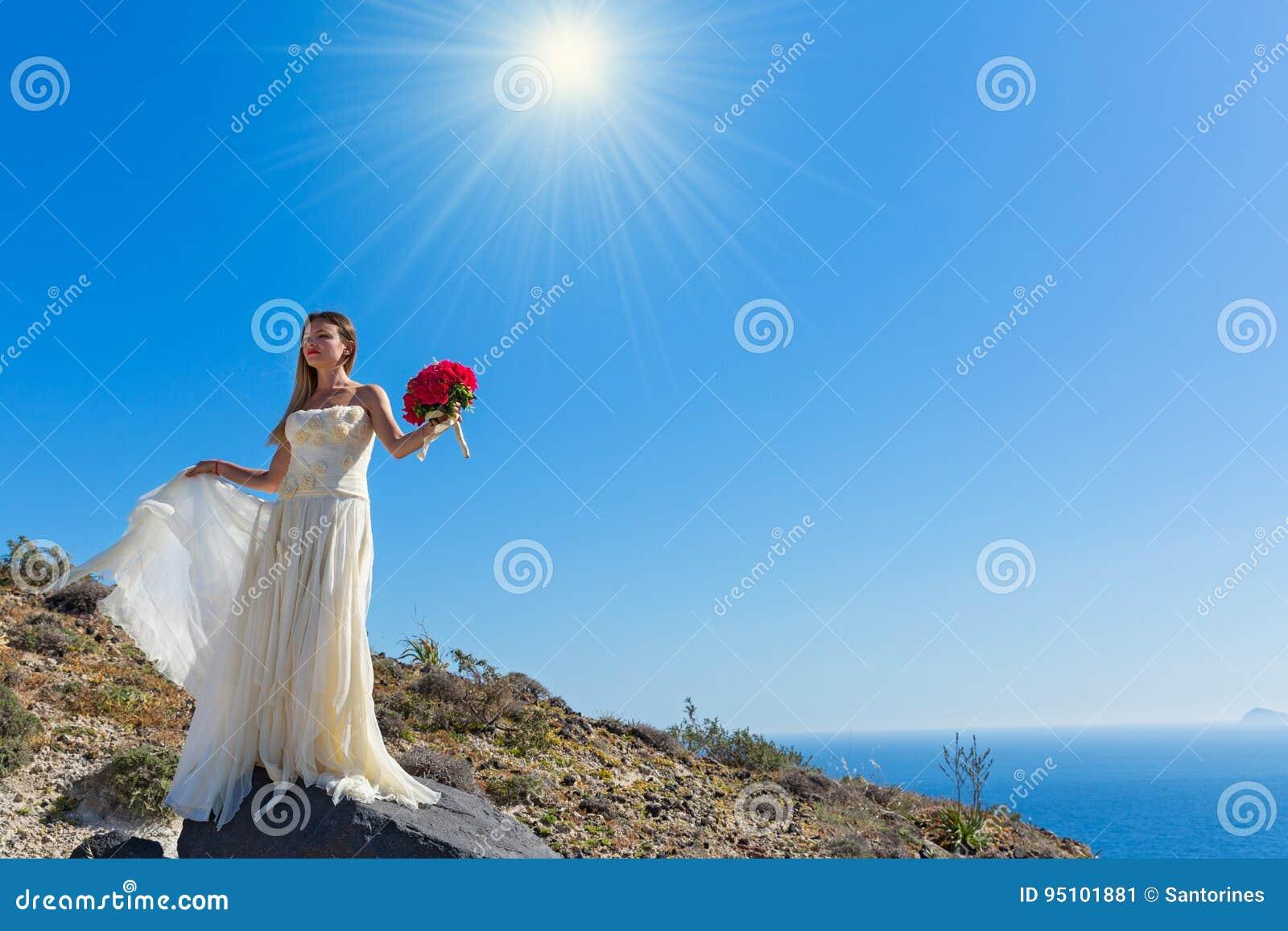 La belle femme se tient sur une haute pierre