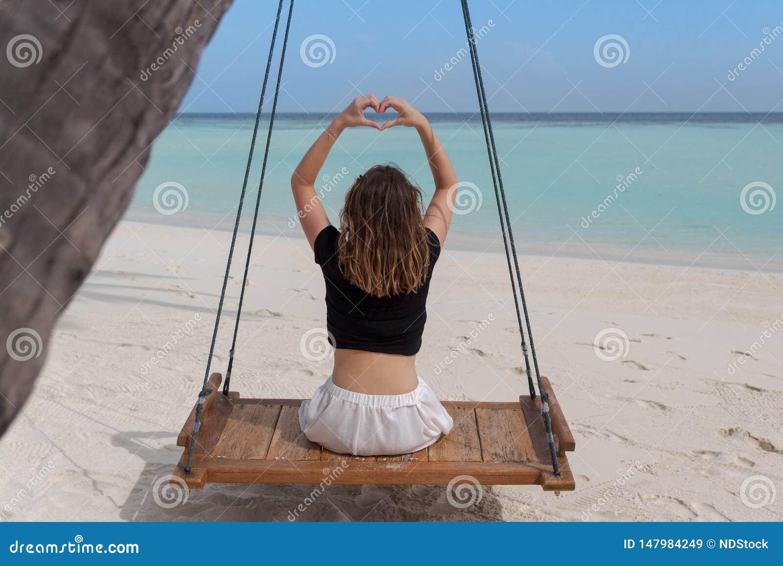 La belle femme sur une oscillation attachée aux cadres d une paume remettent dans la forme de coeur, cadre de coeur de doigt L ea