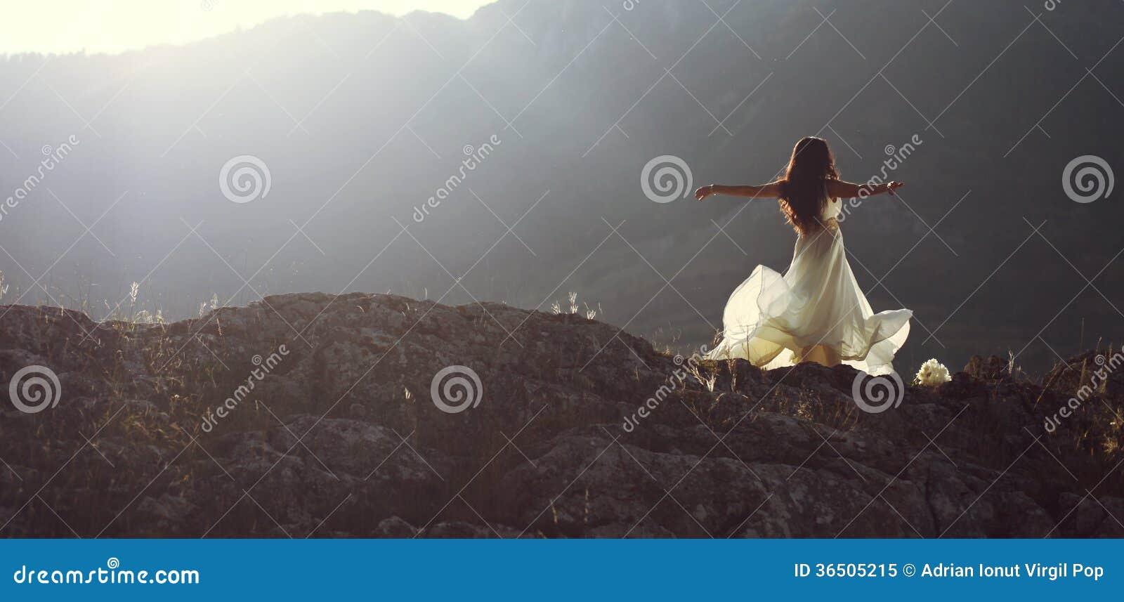 La belle femme tournant avec des bras s ouvrent