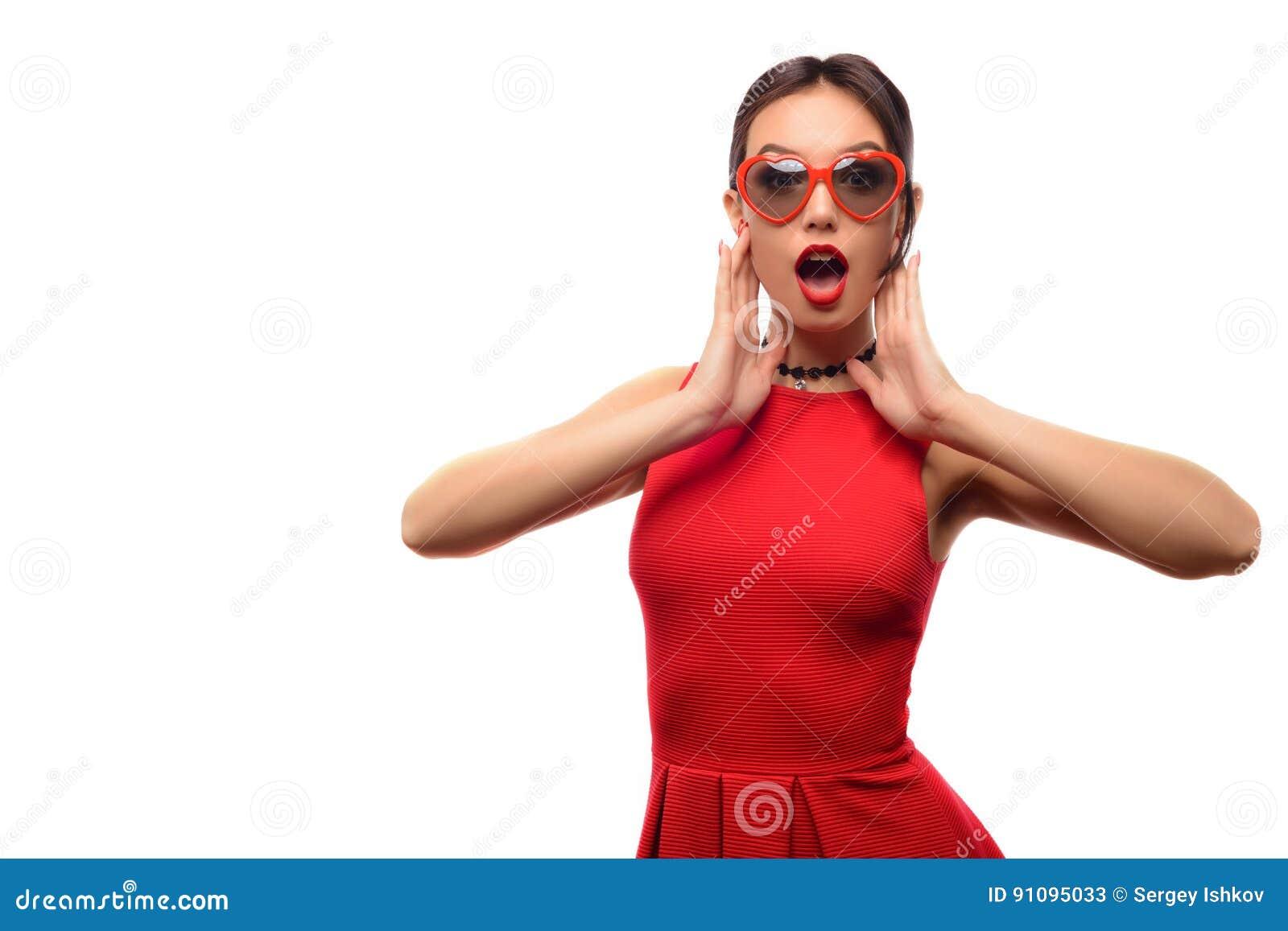 La belle fille attirante dans la robe et des lunettes de soleil rouges sous  forme de coeurs est bouche ouverte avec surprise sur un fond blanc 855d622e1f4
