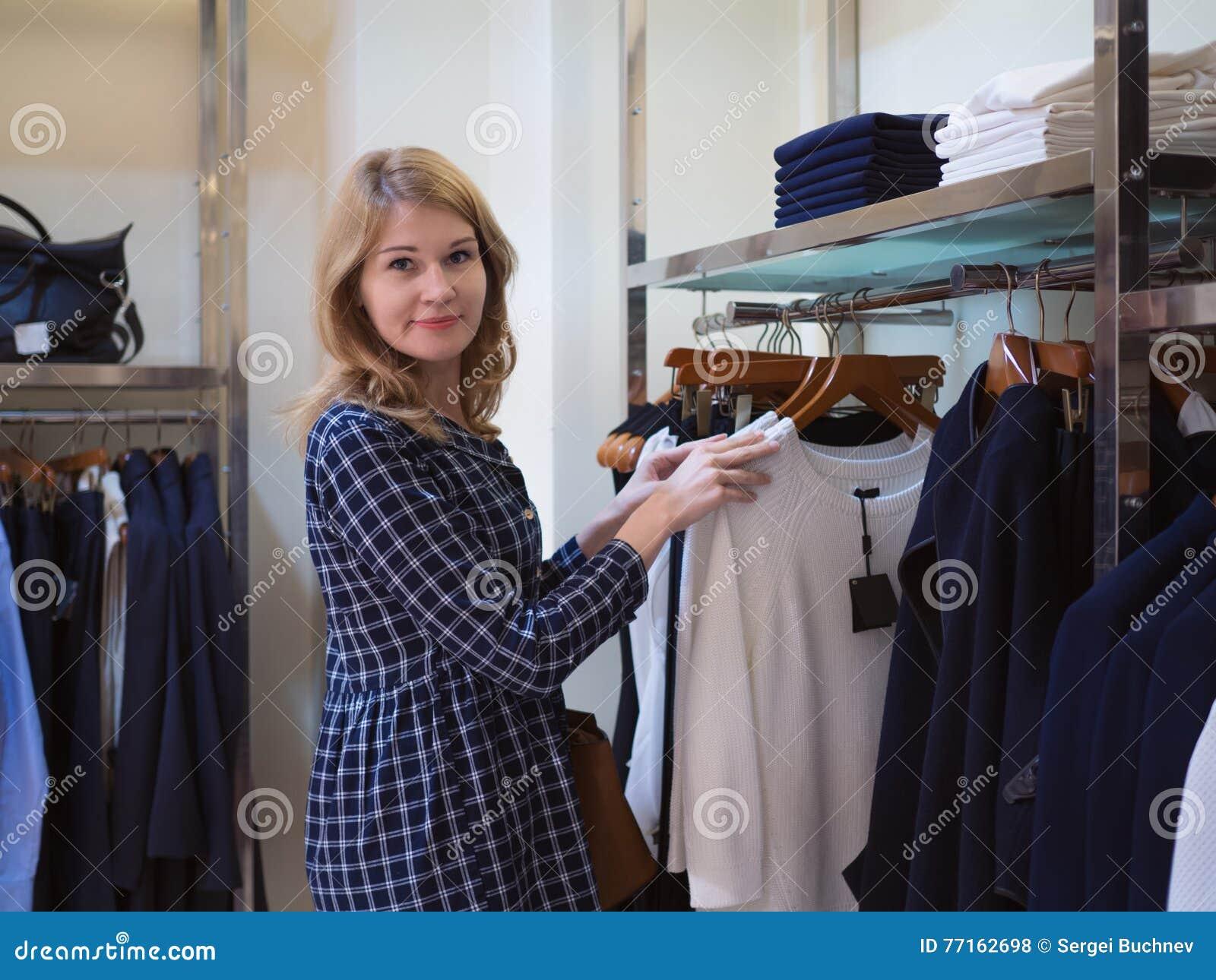 La belle fille choisit des vêtements dans la boutique à la mode Femme dans un Cl