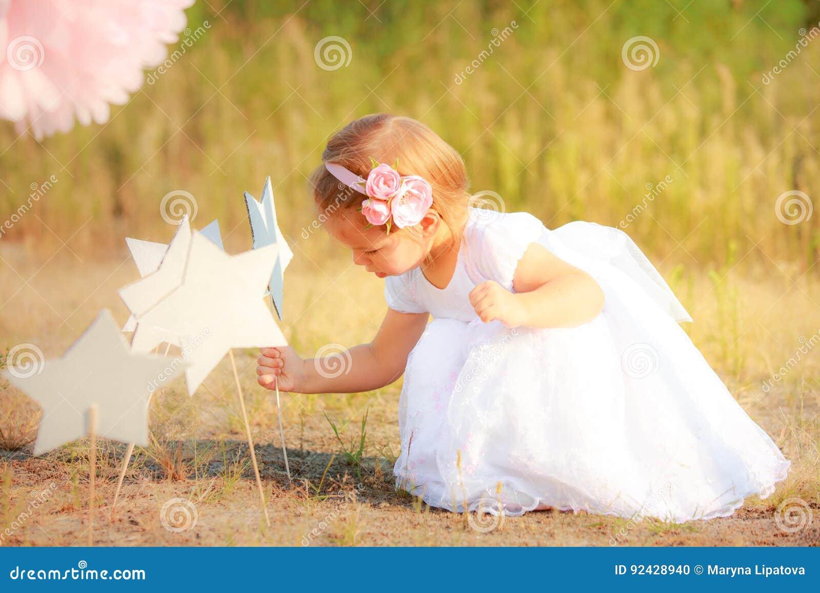 La belle fille dans la longue robe blanche met l étoile de papier sur la terre Enfant sur le fond de la nature