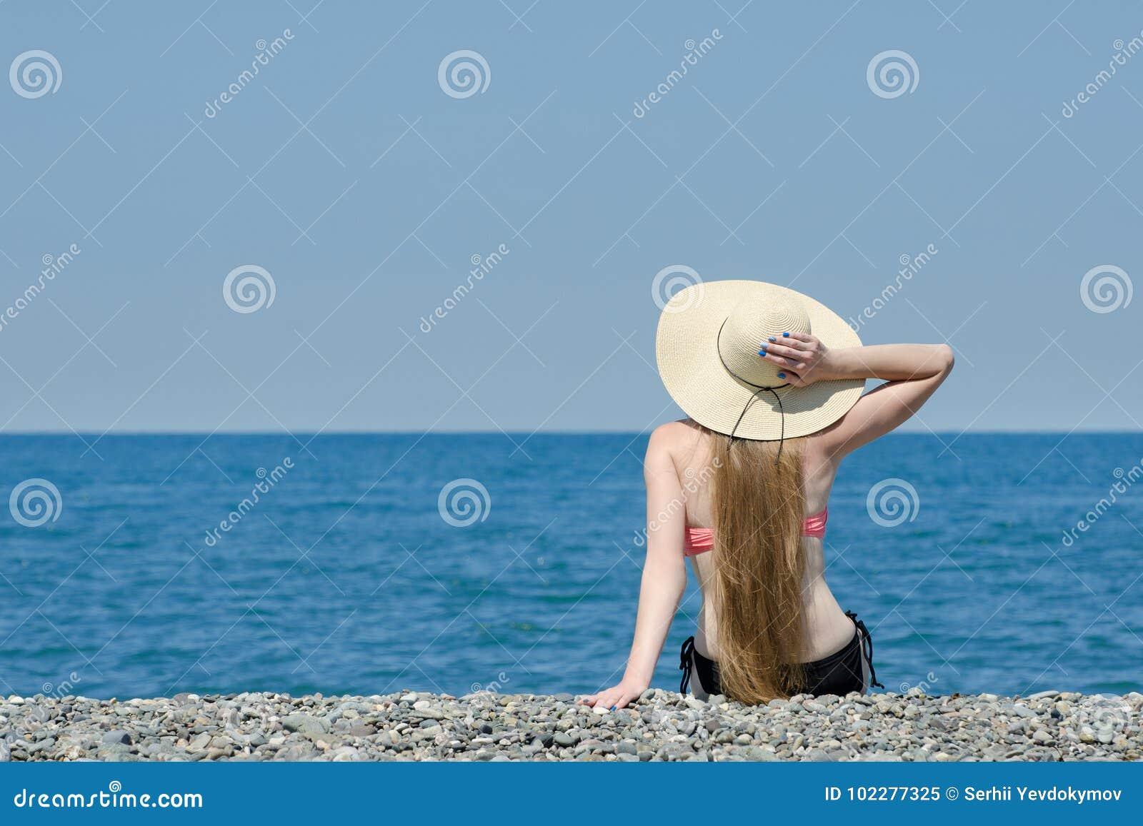 la belle fille dans un chapeau et un maillot de bain s 39 assied sur la plage mer et ciel sur le. Black Bedroom Furniture Sets. Home Design Ideas